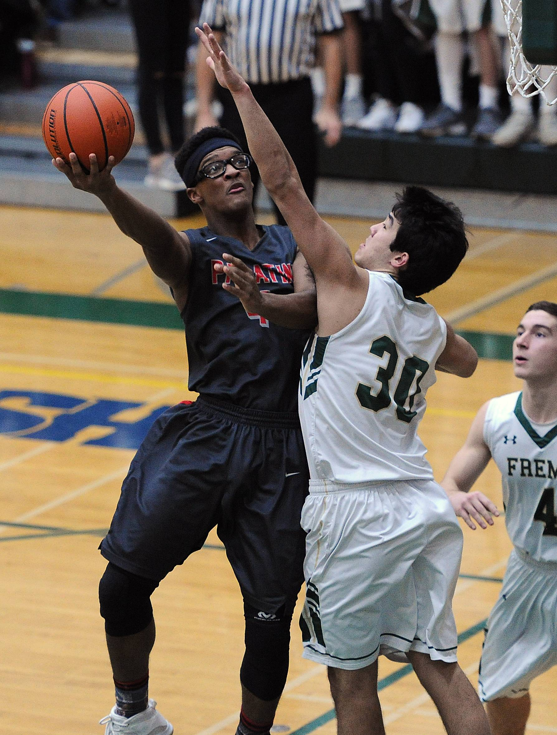 Palatine's Cortez Hogans goes for the score despite pressure from Fremd's Ryan Martin in the first Friday at Fremd.
