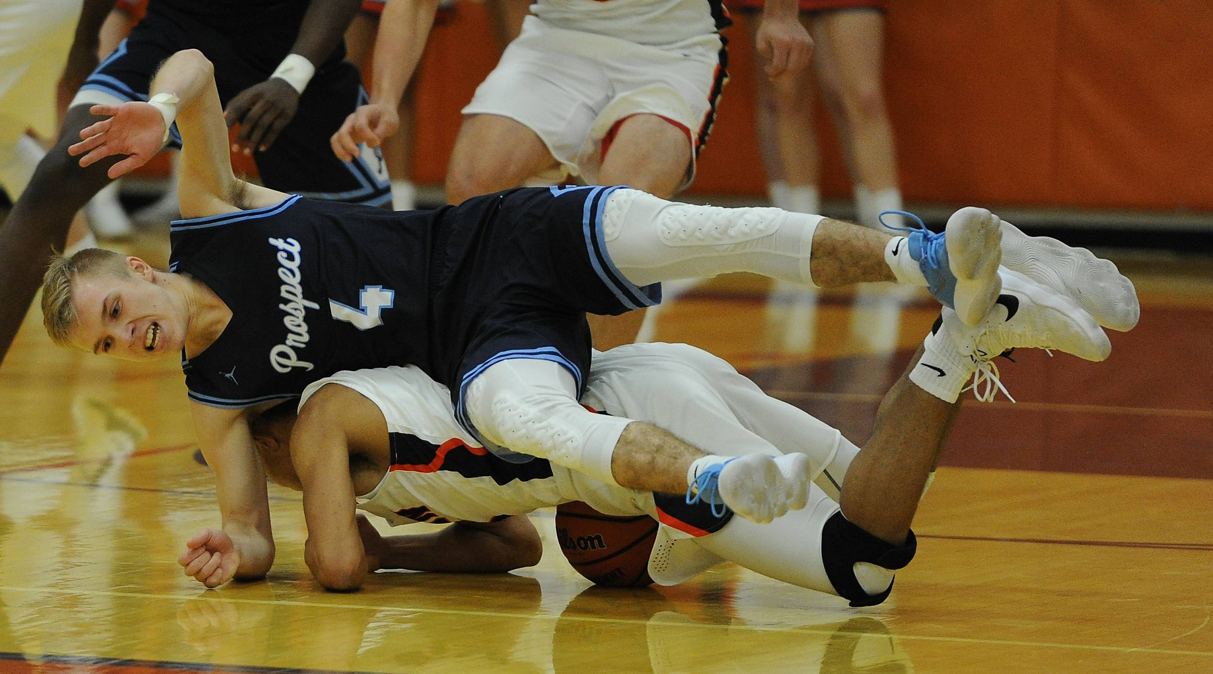 Prospect's David Swedura and Buffalo Grove's Caleb Mayhorn hit the deck after colliding while in pursuit of a loose ball in the first half Friday at Buffalo Grove.