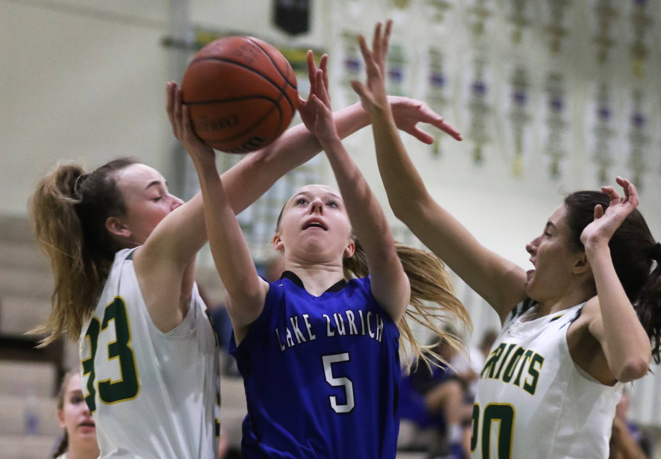 Lake Zurich guard Ella Gilbertson, center, is fouled by Stevenson players Klaire Steffens, left, and Avery King on Thursday at Stevenson.