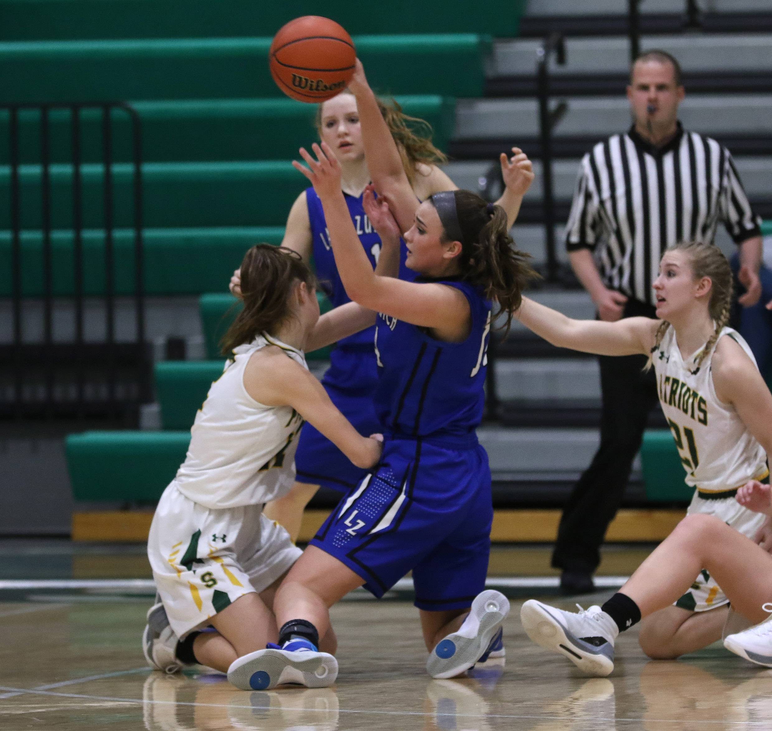 Lake Zurich guard McKenna Zobel tries to throw the ball from her knees past Stevenson players Krissy Hill, left, and Julia Osuch on Thursday at Stevenson.