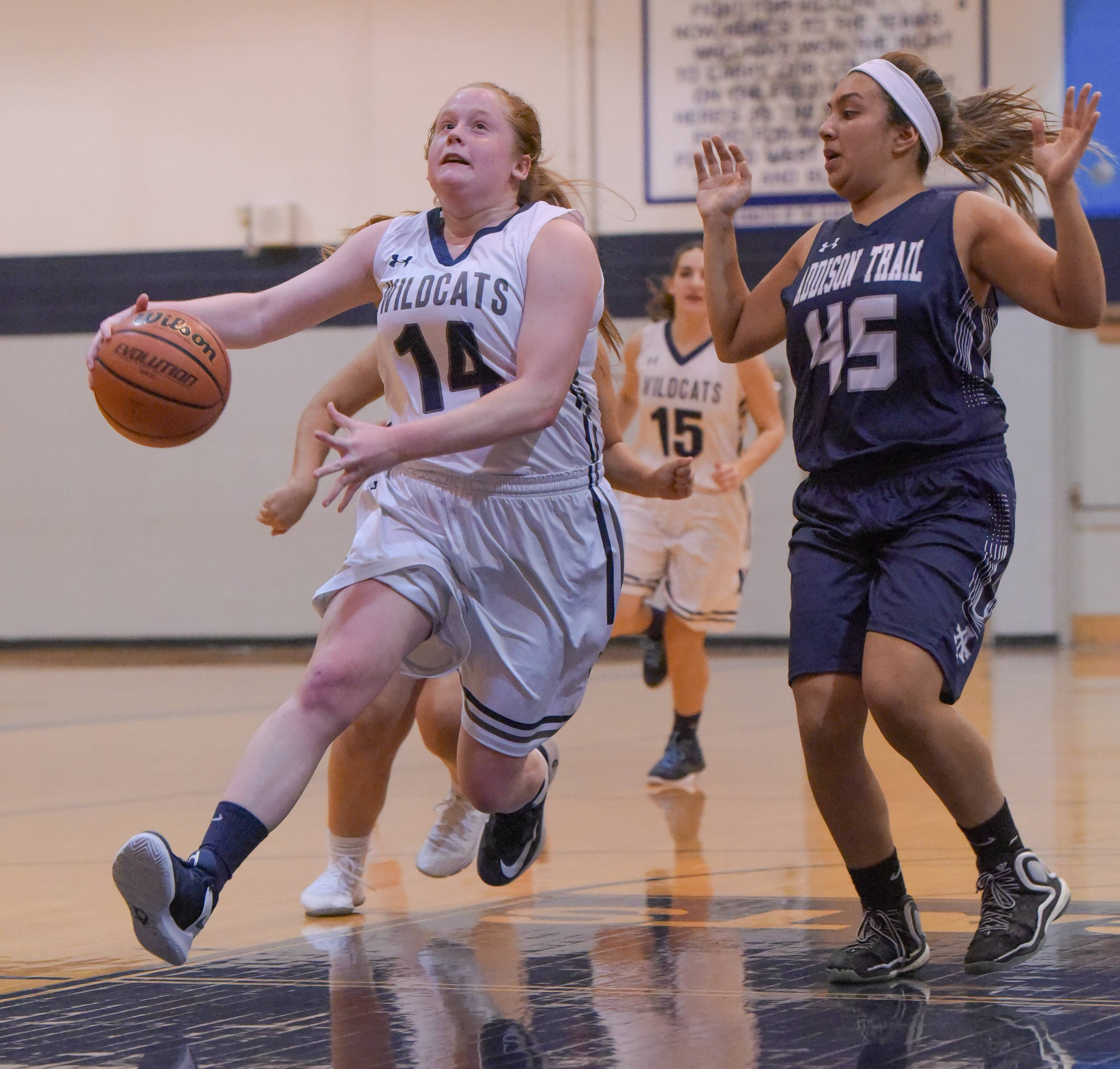 West Chicago's Sam Wiegele (14) drives toward the hoop after getting past Addison Trail's Berenice Berumen (45) during varsity girls basketball in West Chicago on January 9, 2018.