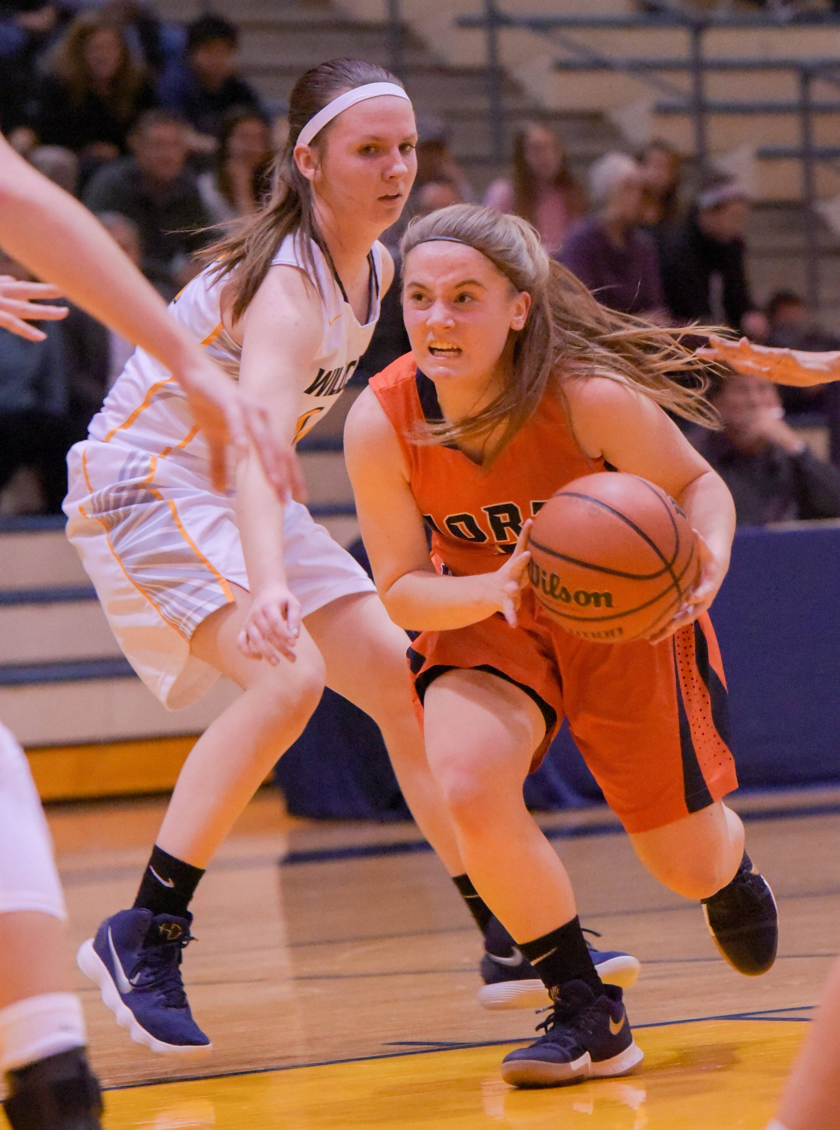 Naperville North's Kara Rivard drives past Neuqua Valley's Taylor Crowley during girls basketball at on Wednesday, Jan. 10, 2018.