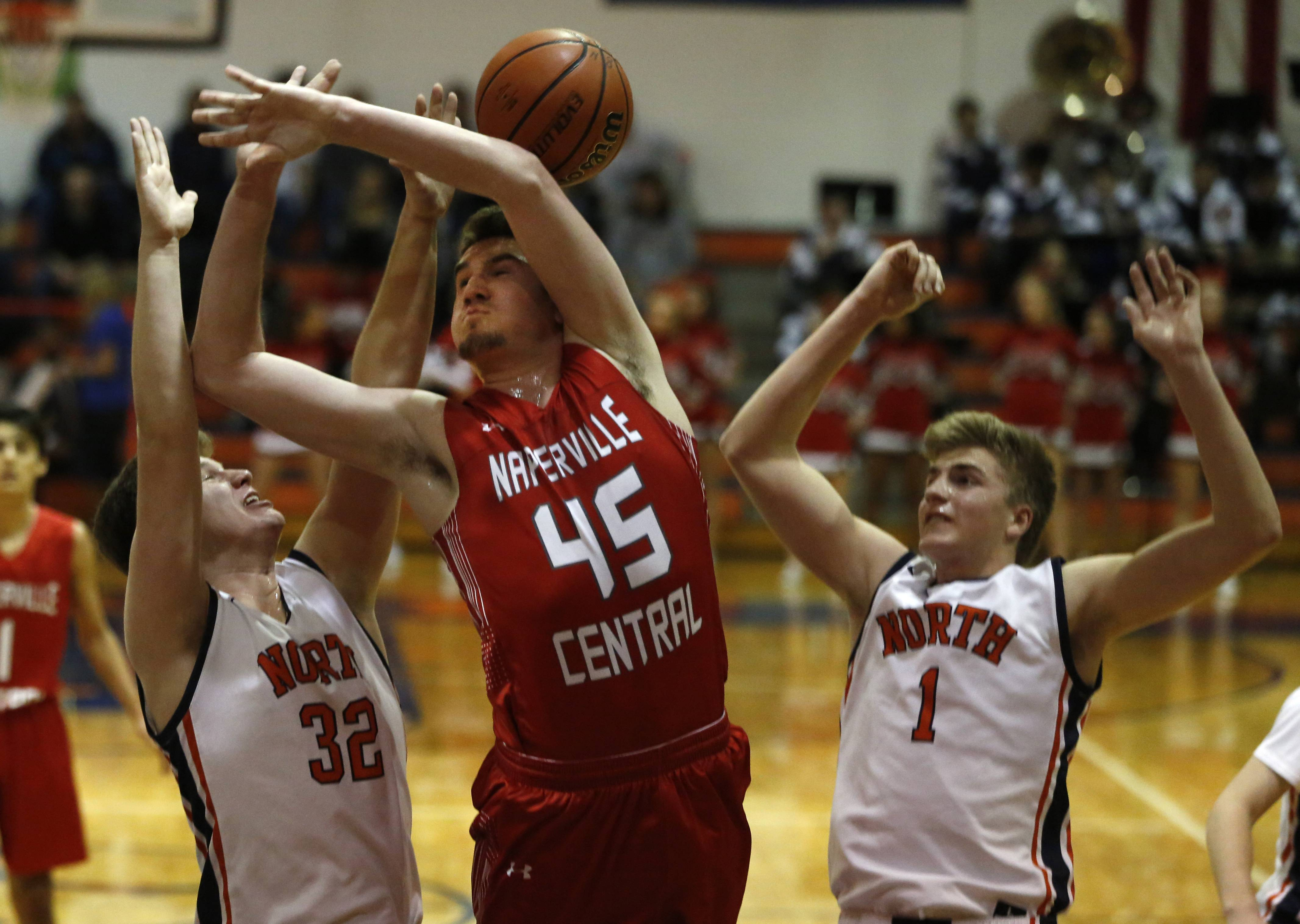 Naperville Central's Benjamin Wolf (45) battles Naperville North's Chris Johnson (32) and Tom Welch (1) during boys basketball action in Naperville.