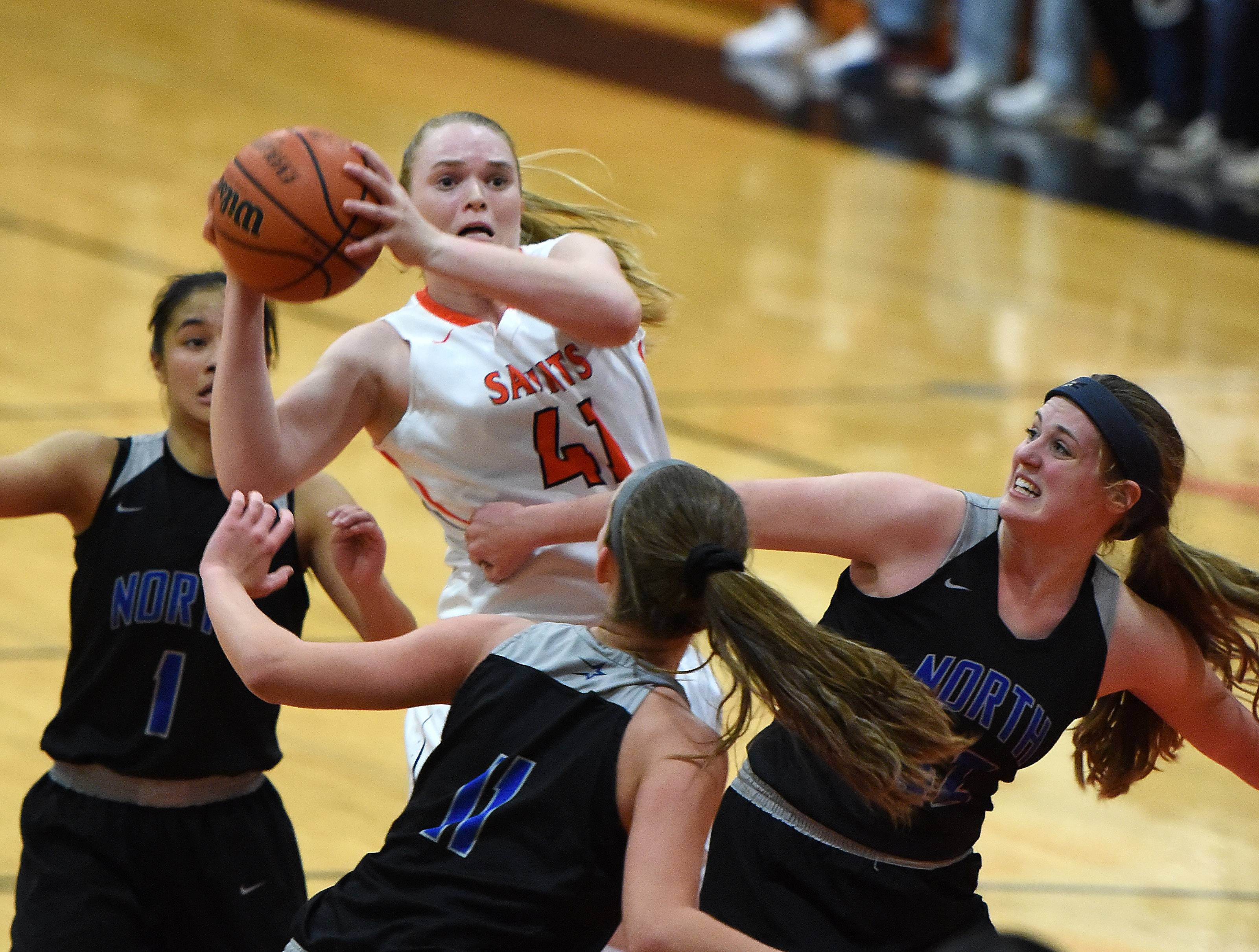St. Charles East's Sara Rosenfeldt goes up for an off-balanced shot as she's surrounded by three St. Charles North defenders during Friday's game at East.