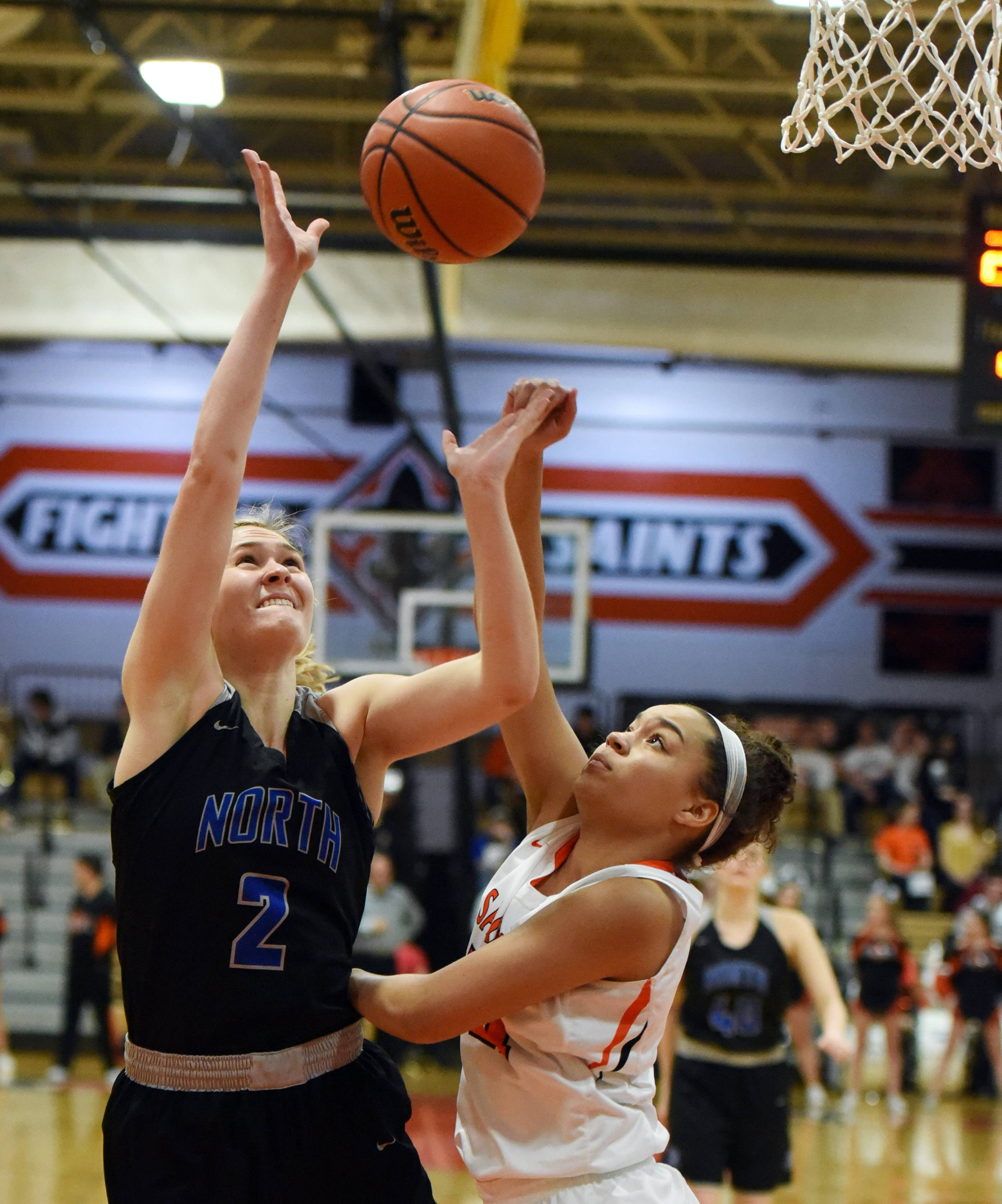 St. Charles North's Anna Davern is fouled by St. Charles East's Taylor Shead during Friday's game at East.