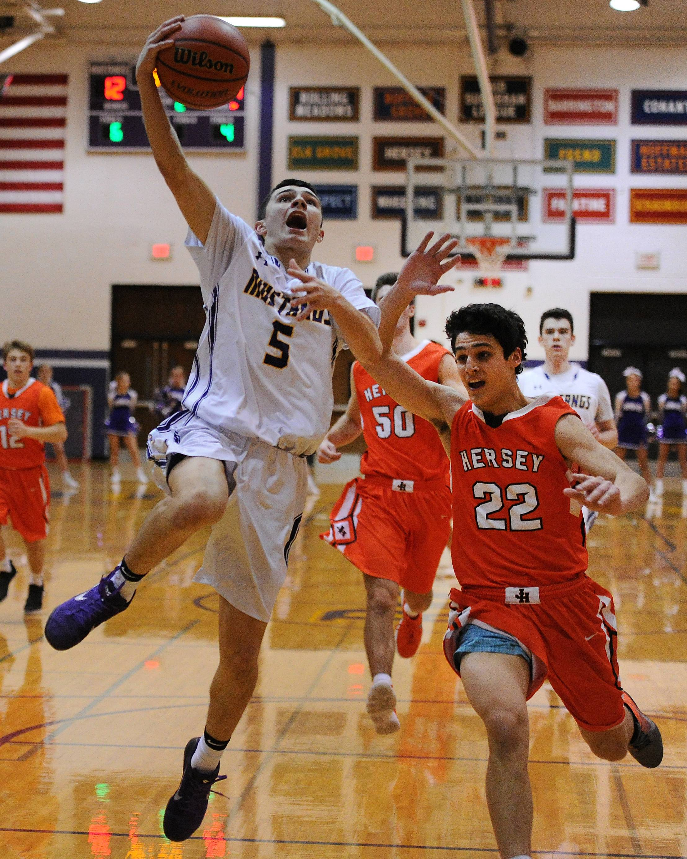 Rolling Meadows' Willis Goodwin delivers a basket despite pressure from Hersey's Jace Coffaro in the first half at Rolling Meadows on Friday.