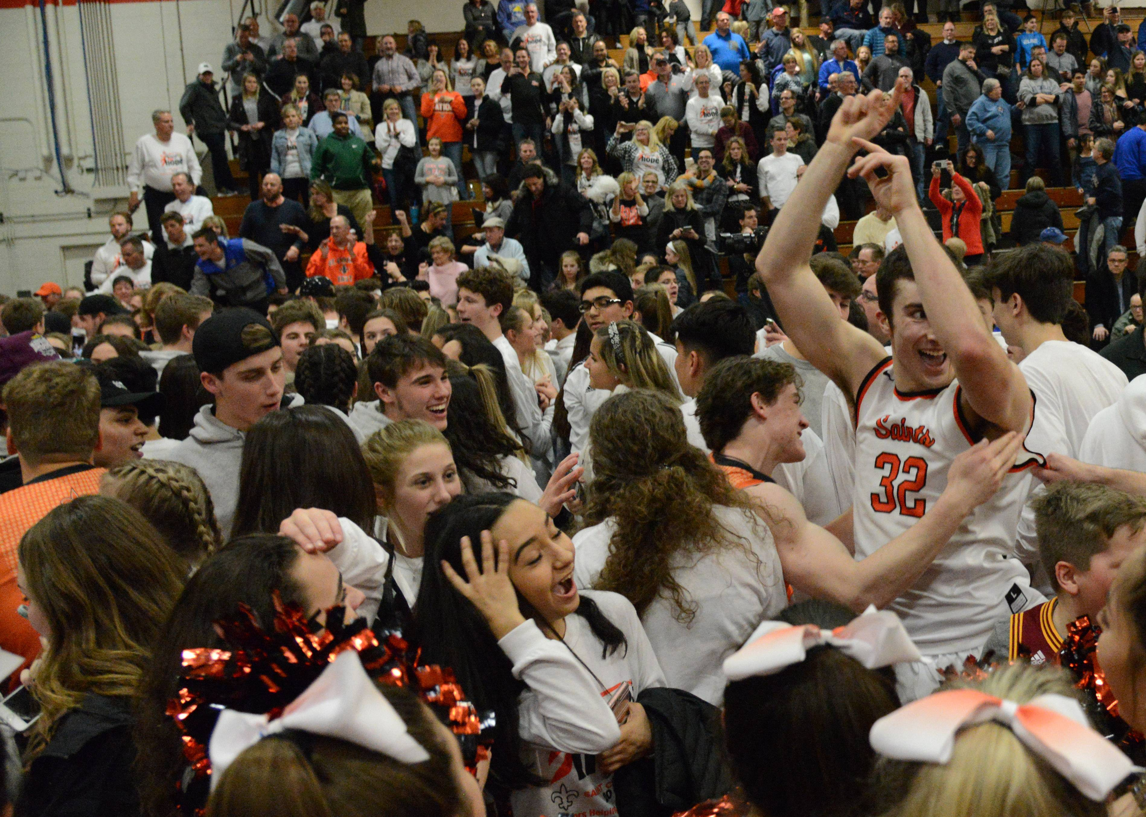 St. Charles East fans surround Justin Hardy after his last second shot beat rival St. Charles North during Friday's game at East.