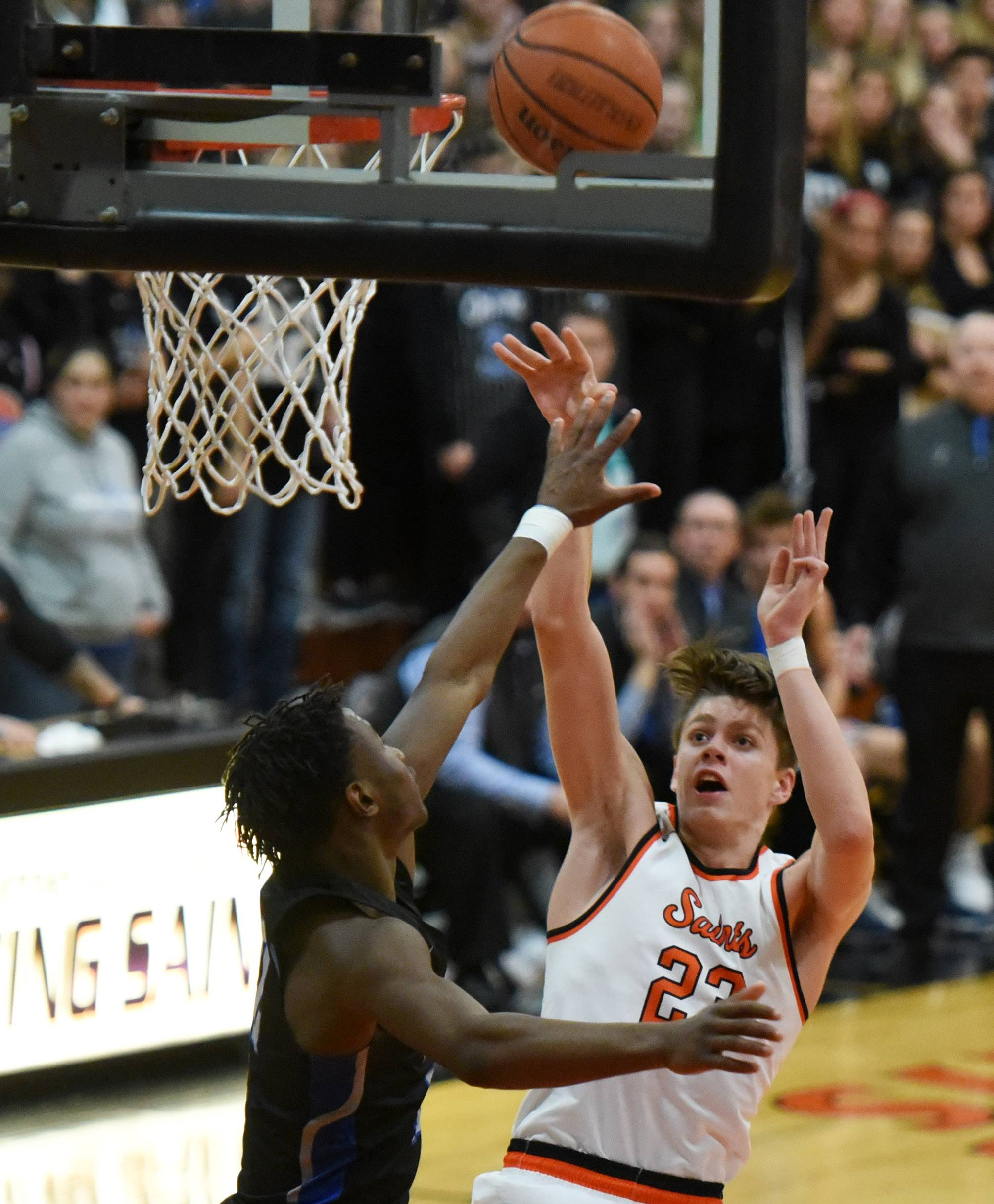 St. Charles East's Cody Mitchell puts up a shot over St. Charles North's Tyler Nubin during Friday's game at East.