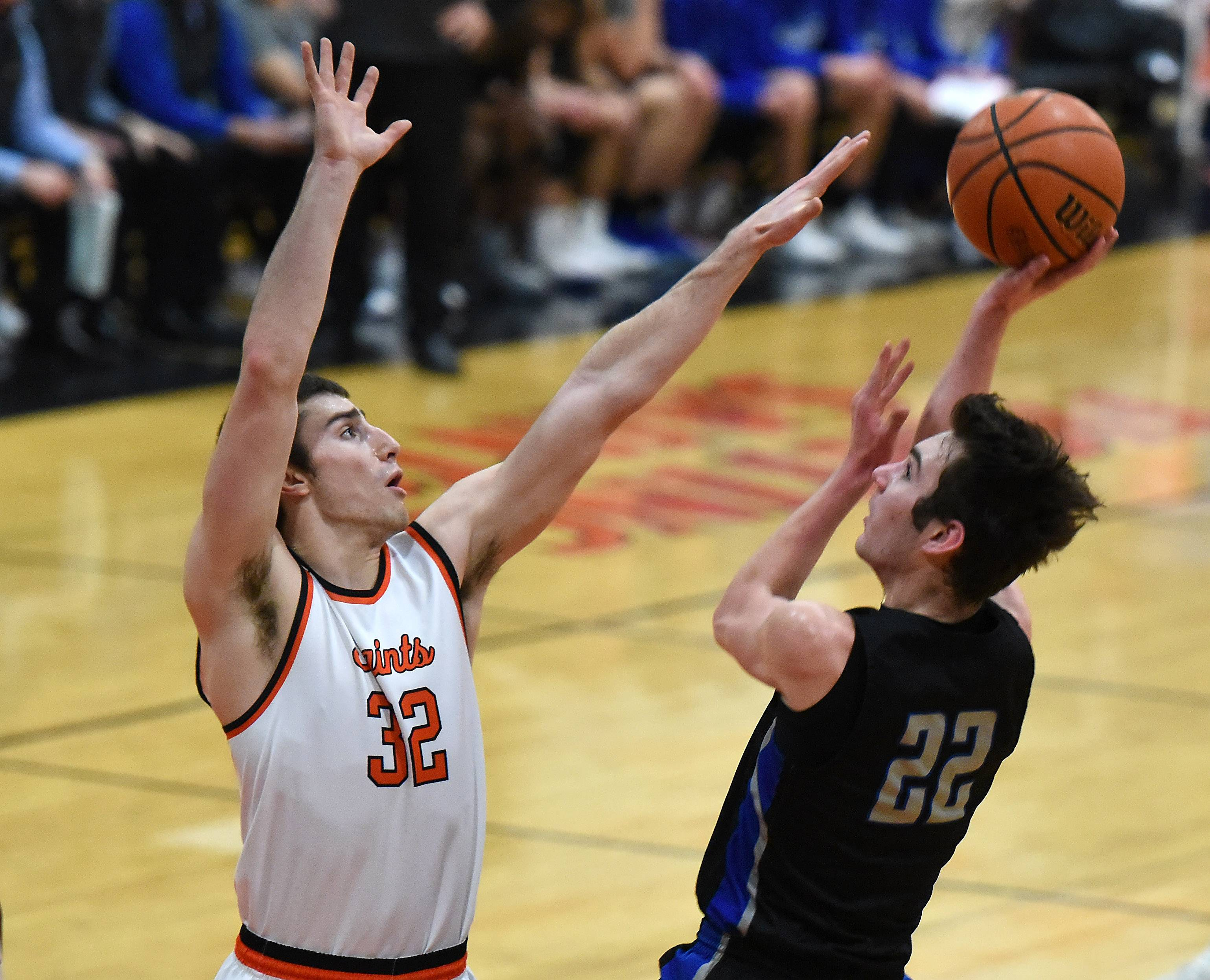 Rick West/rwest@dailyherald.comSt. Charles East's Justin Hardy tries to block the shot of St. Charles North's Cade Callaghan during Friday's game at East.