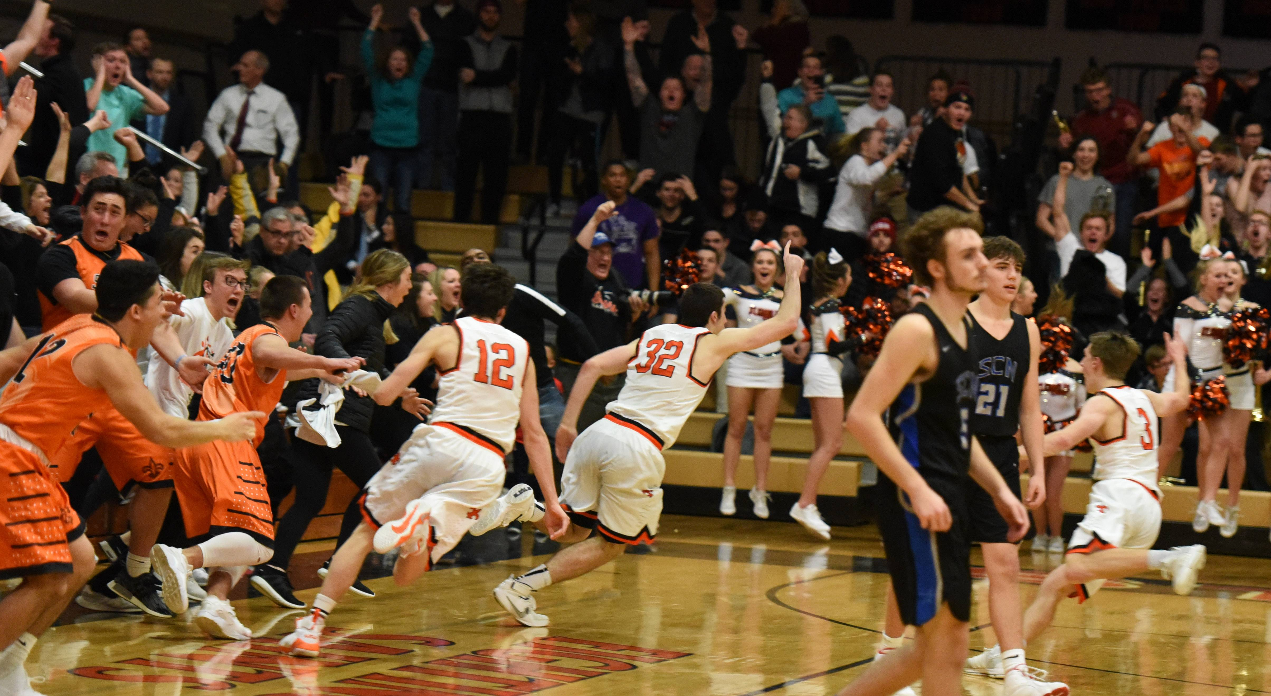 Above: St. Charles East's Justin Hardy (32) races off the court as the fans storm out of the stands following his last-second shot to beat St. Charles North during Friday's game at East. Below: Hardy celebrates with his teammates and Saints fans.