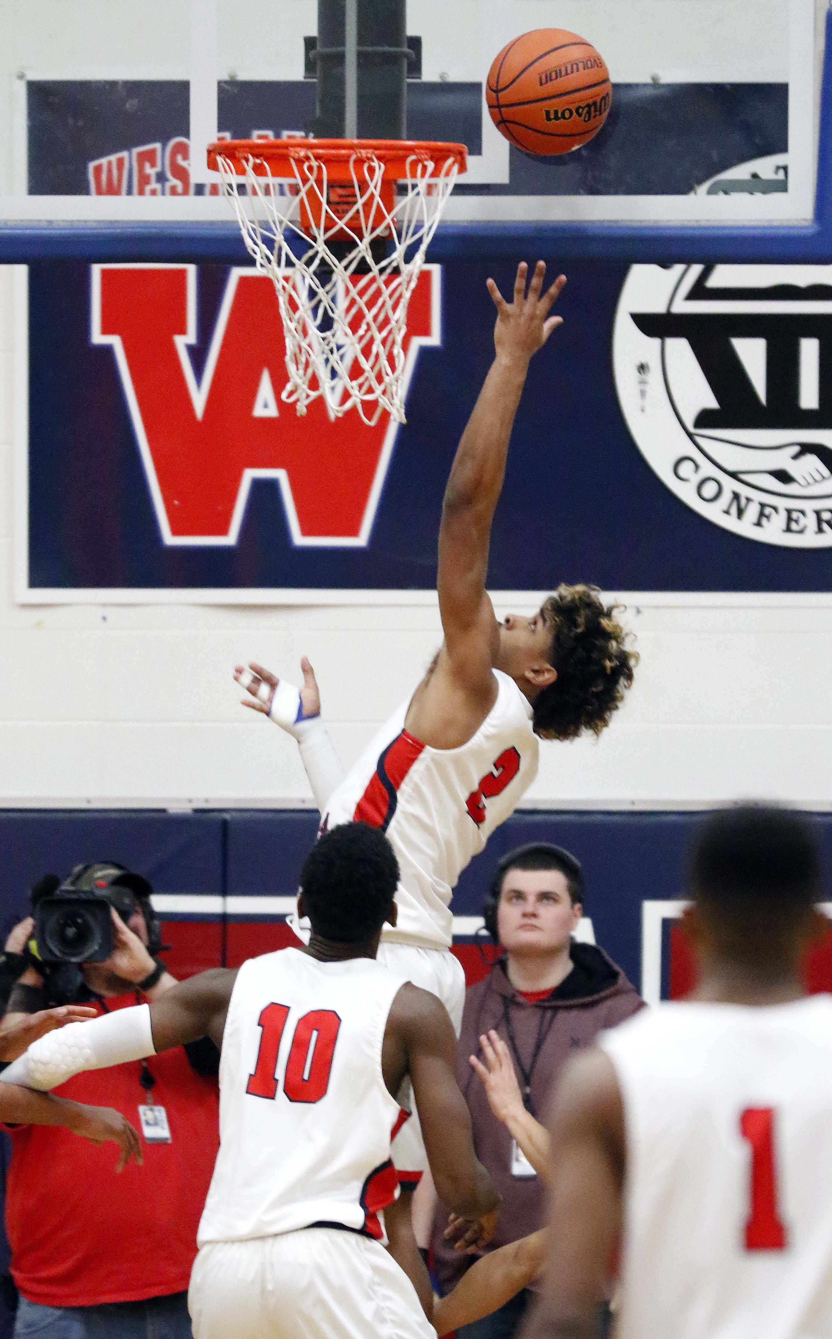 West Aurora guard Camron Donatlan goes to the hoop Saturday during basketball at West Aurora High School.