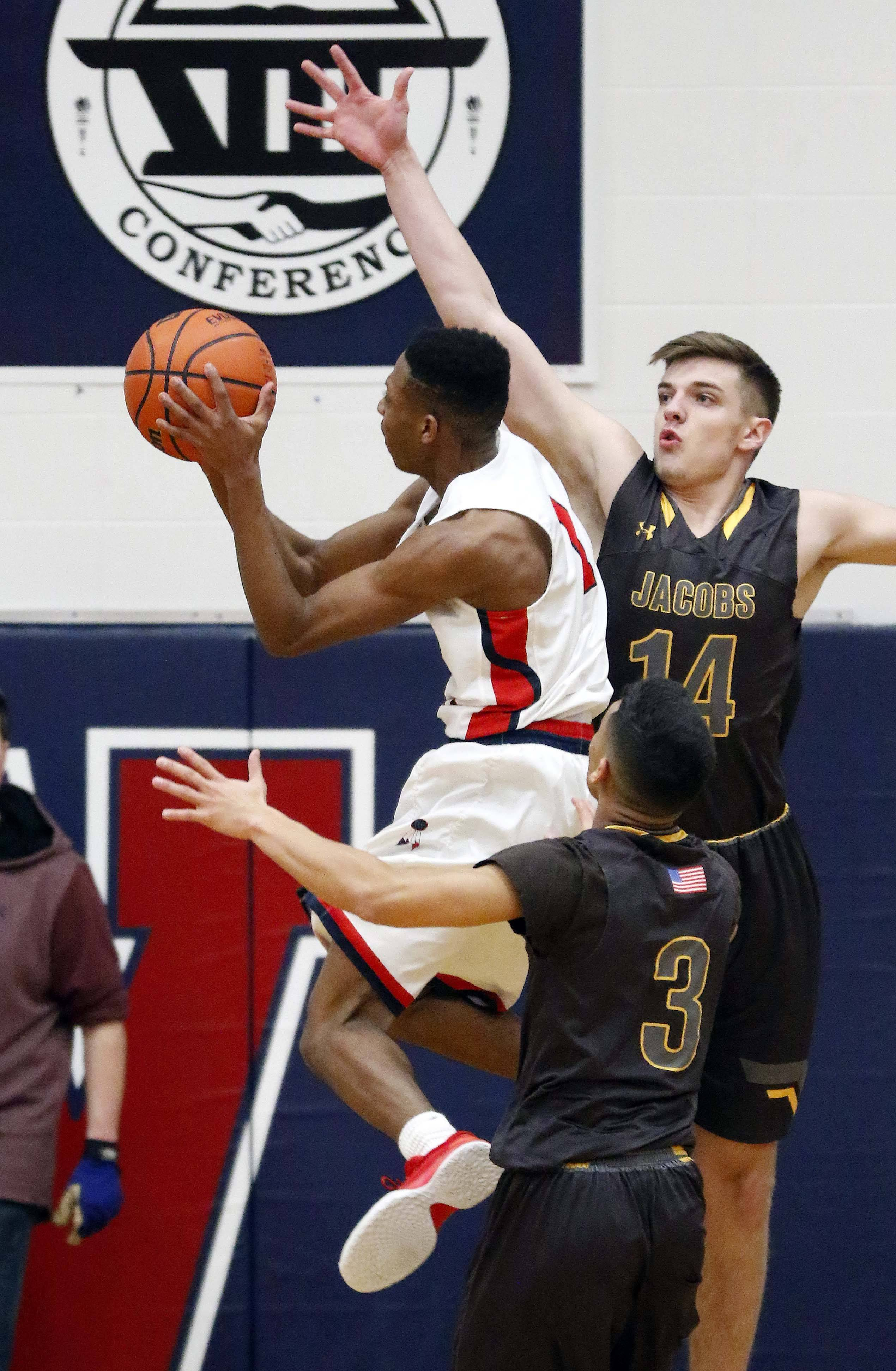 West Aurora guard Traevon Brown goes to the hoop past Jacobs guards Ajani Rodriguez and Ryan Phillips Saturday during basketball at West Aurora High School.