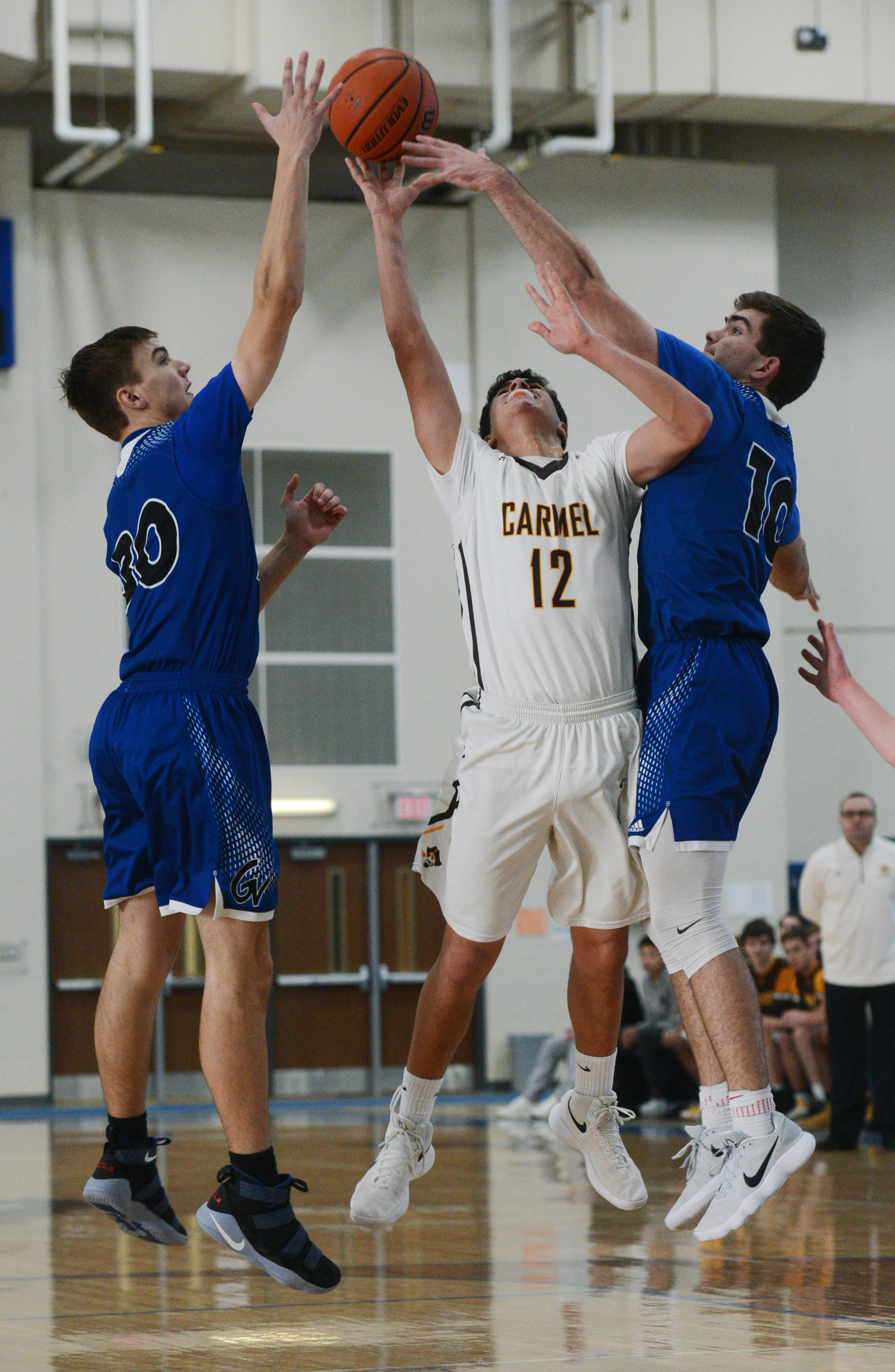 Carmel's Evan Myers manages to release a shot between the tight defense of Geneva's Joshua Preston, left, and Jack Hood during the Lake Zurich Martin Luther King Classic on Saturday.