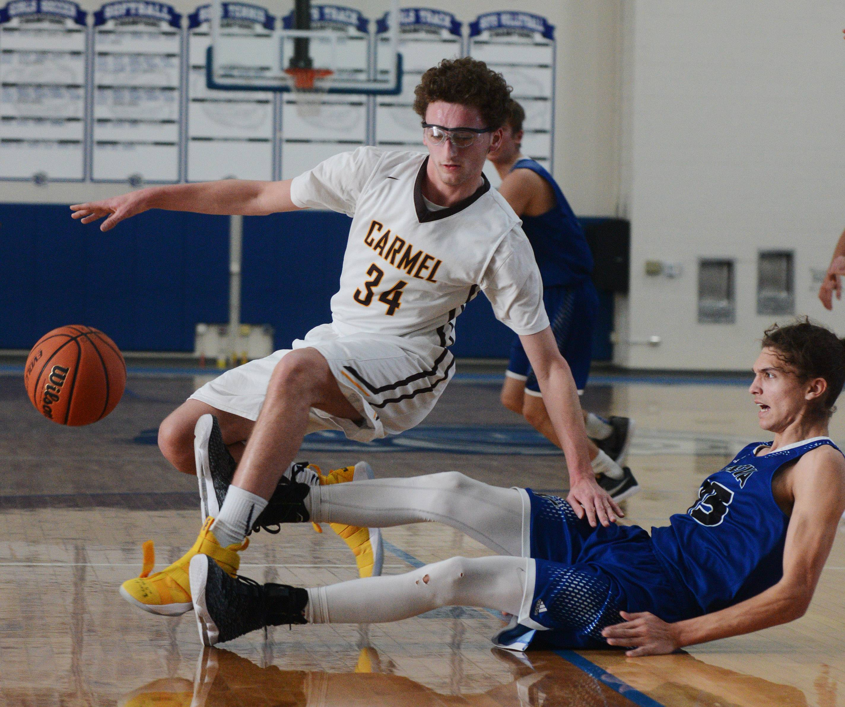 Carmel's Jonathan Roeser, left, is called for charging on a move to the basket against Geneva's Kross Garth during the Lake Zurich Martin Luther King Classic on Saturday.