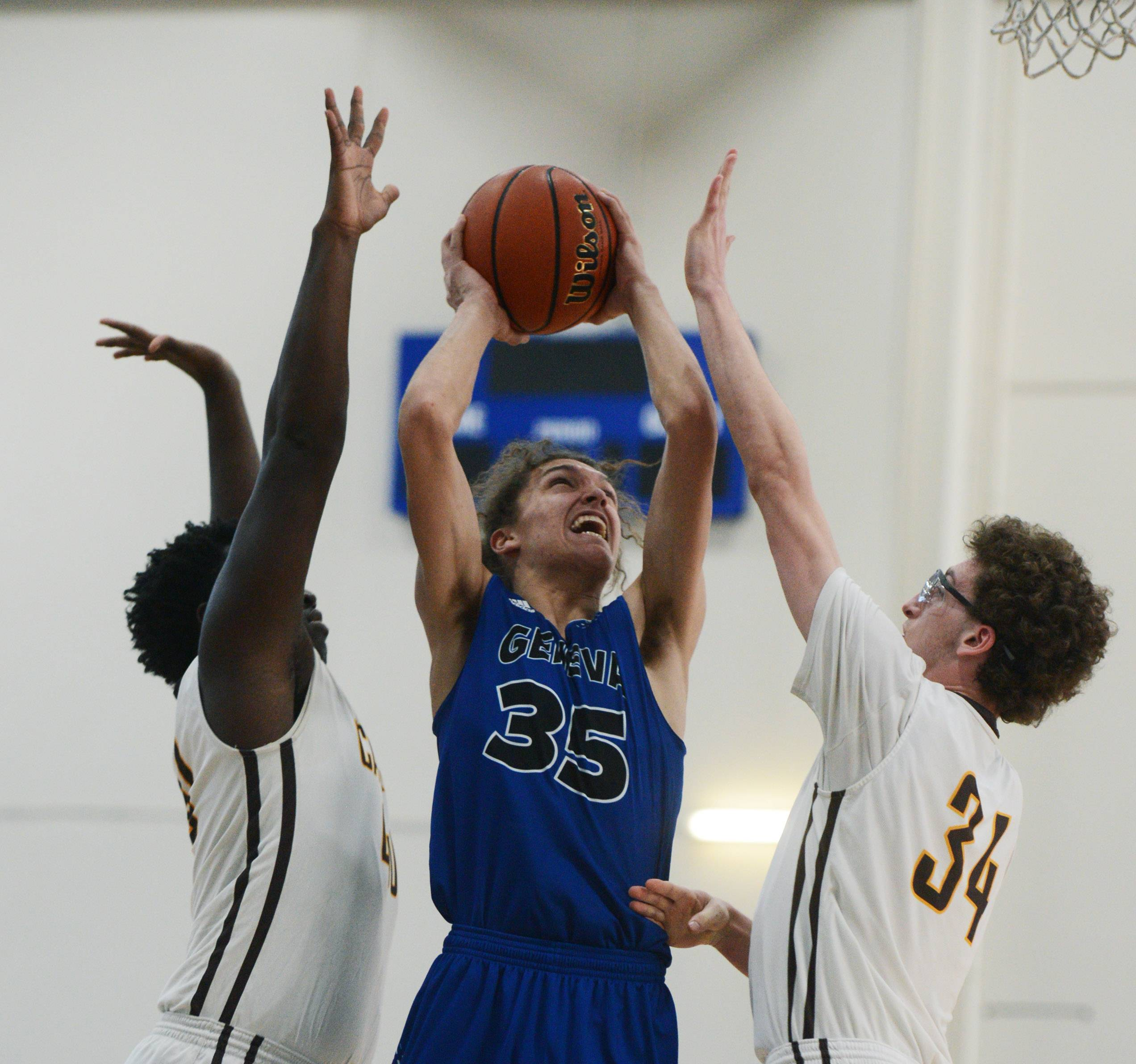 Geneva's Kross Garth shoots between Carmel defenders Jalen Snell, left, and Jonathan Roeser during the Lake Zurich Martin Luther King Classic on Saturday.