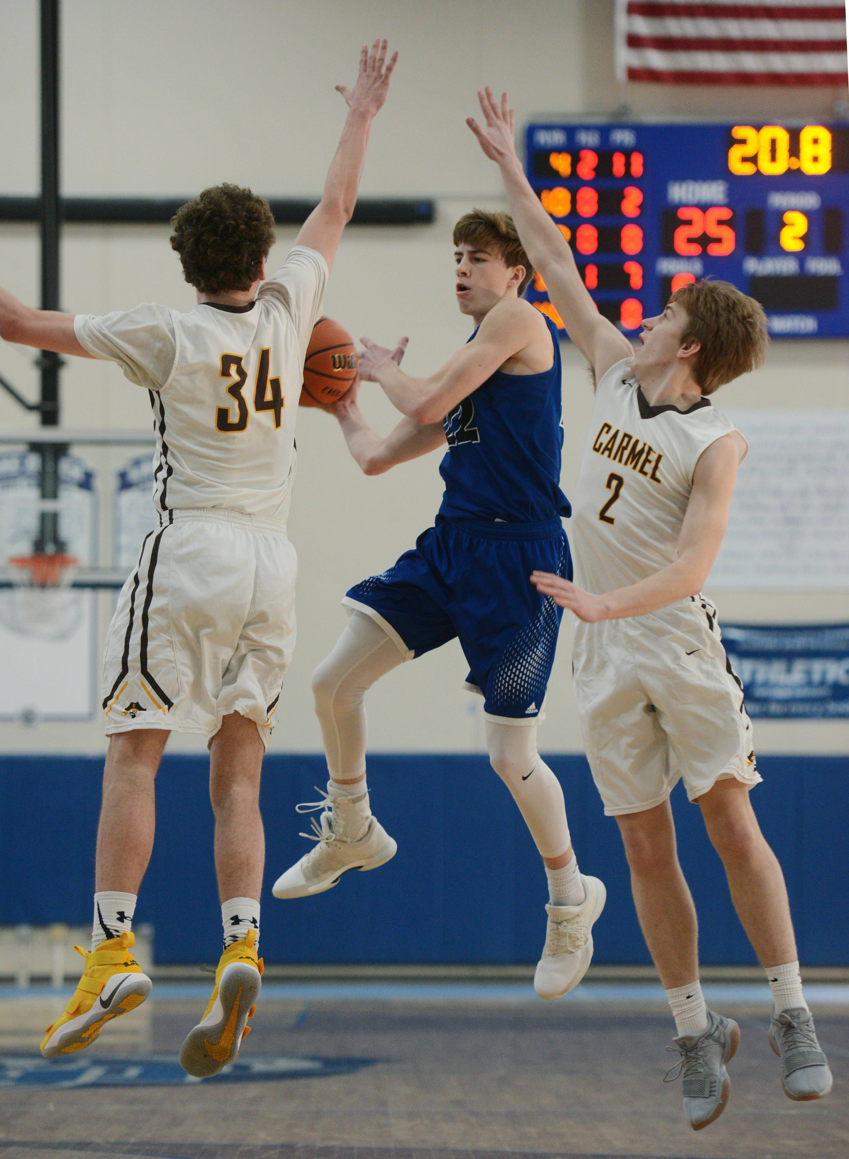 Geneva's Mitch Mascari passes as Carmel defenders Jonathan Roeser, left, and Matthew Brolley close in during the Lake Zurich Martin Luther King Classic on Saturday.