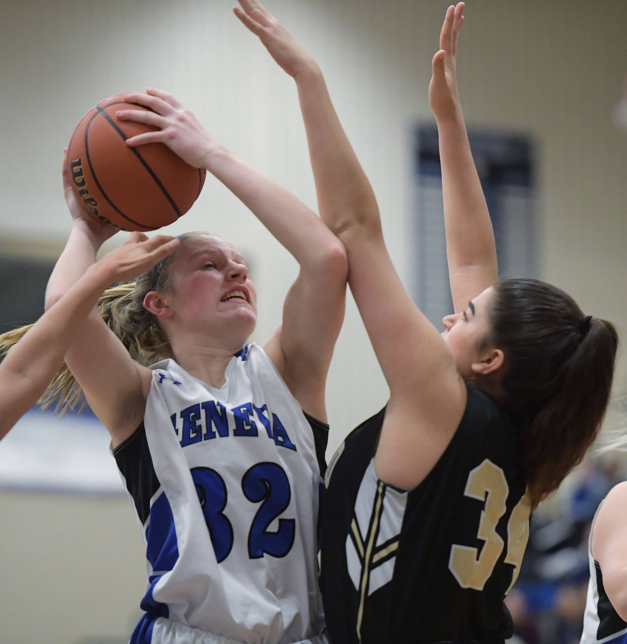 Geneva's Lindsay Blackmore is stopped under the basket by Streamwood's Alexis Rojas and Mandy Mien during a girls basketball game Tuesday in Geneva.