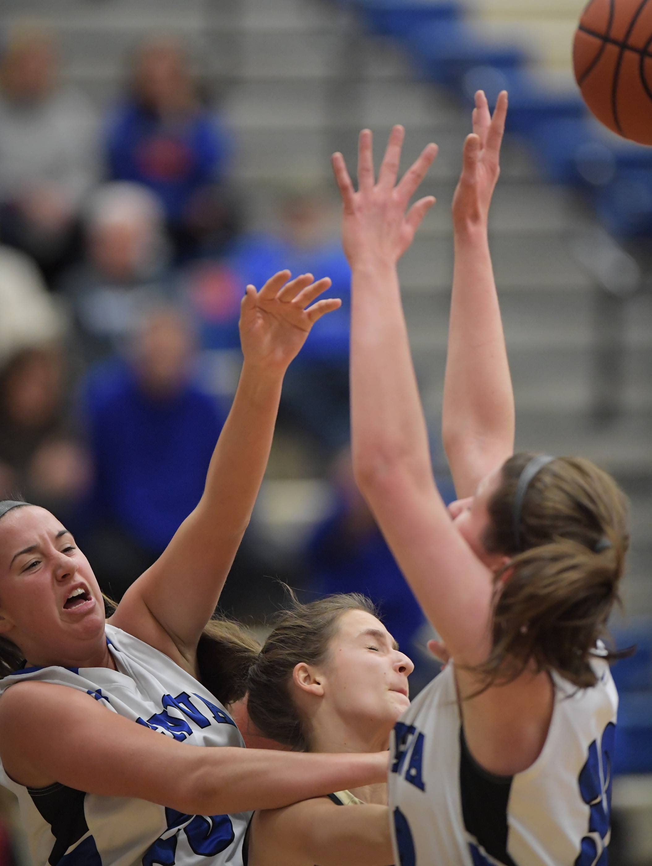 Geneva's Margaret Whitley, left, and Madison Mallory sandwich Streamwood's Maddi Exline as the trio battle for a rebound during a girls basketball game Tuesday in Geneva.