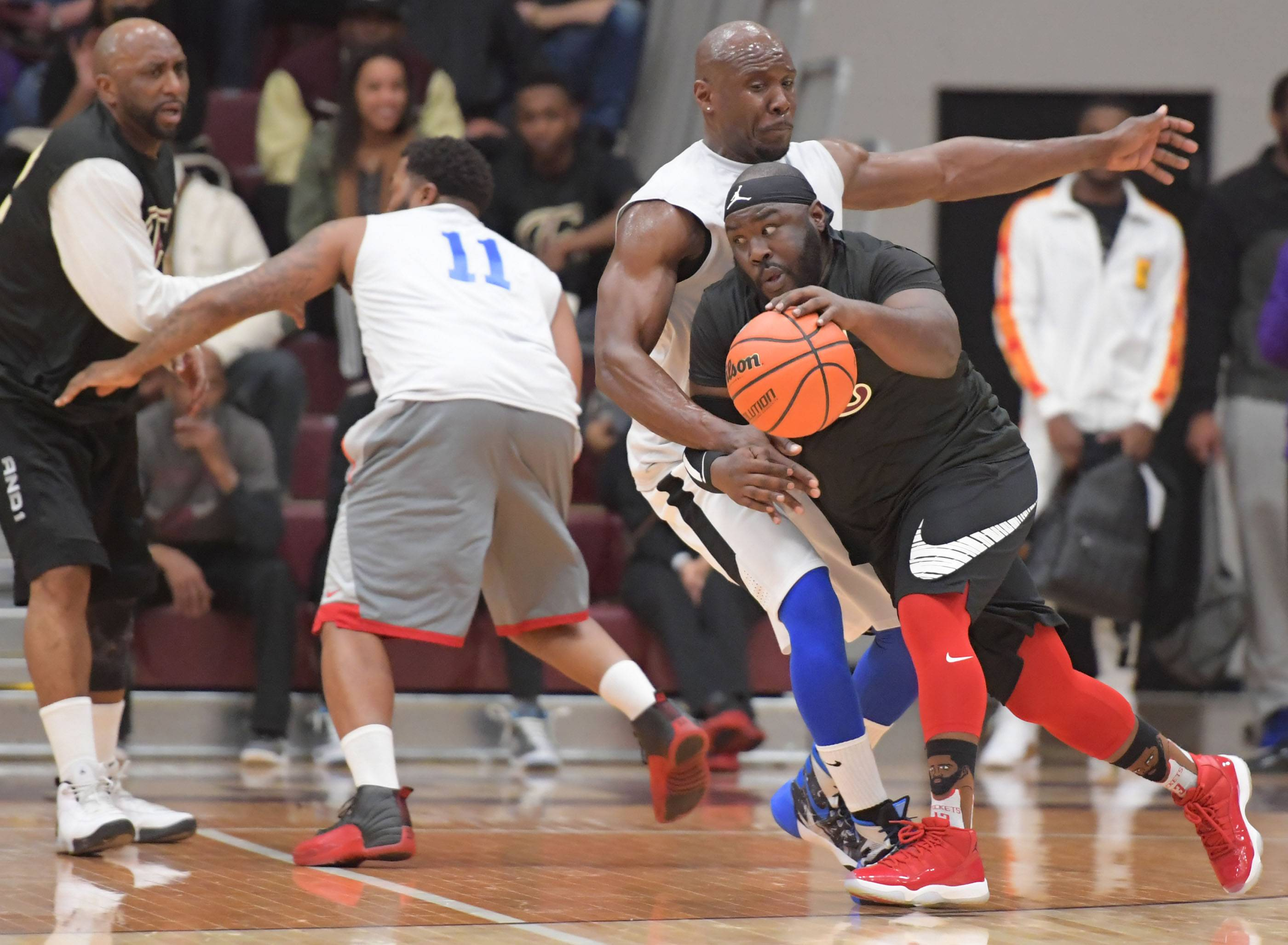 Javell Cooks, an Elgin High School alum, drives into Larkin alum David Binion at the Elgin High School vs. Larkin High School Alumni basketball game at Chesbrough Field House at Elgin High School Wednesday night.