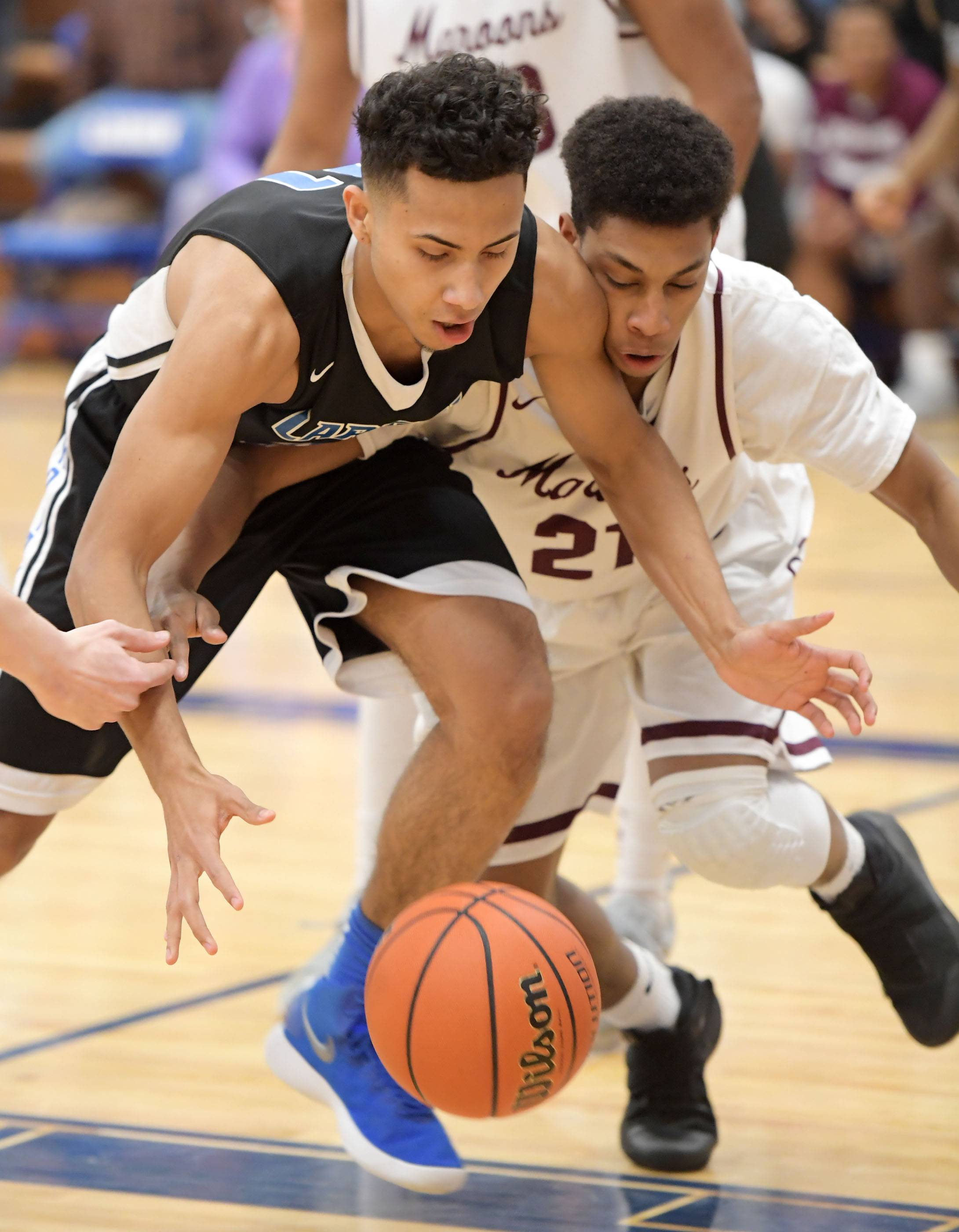 Larkin's Anthony Lynch and Elgin's Michael Weatherburn compete for the ball Friday in a boys basketball game at Larkin High School.