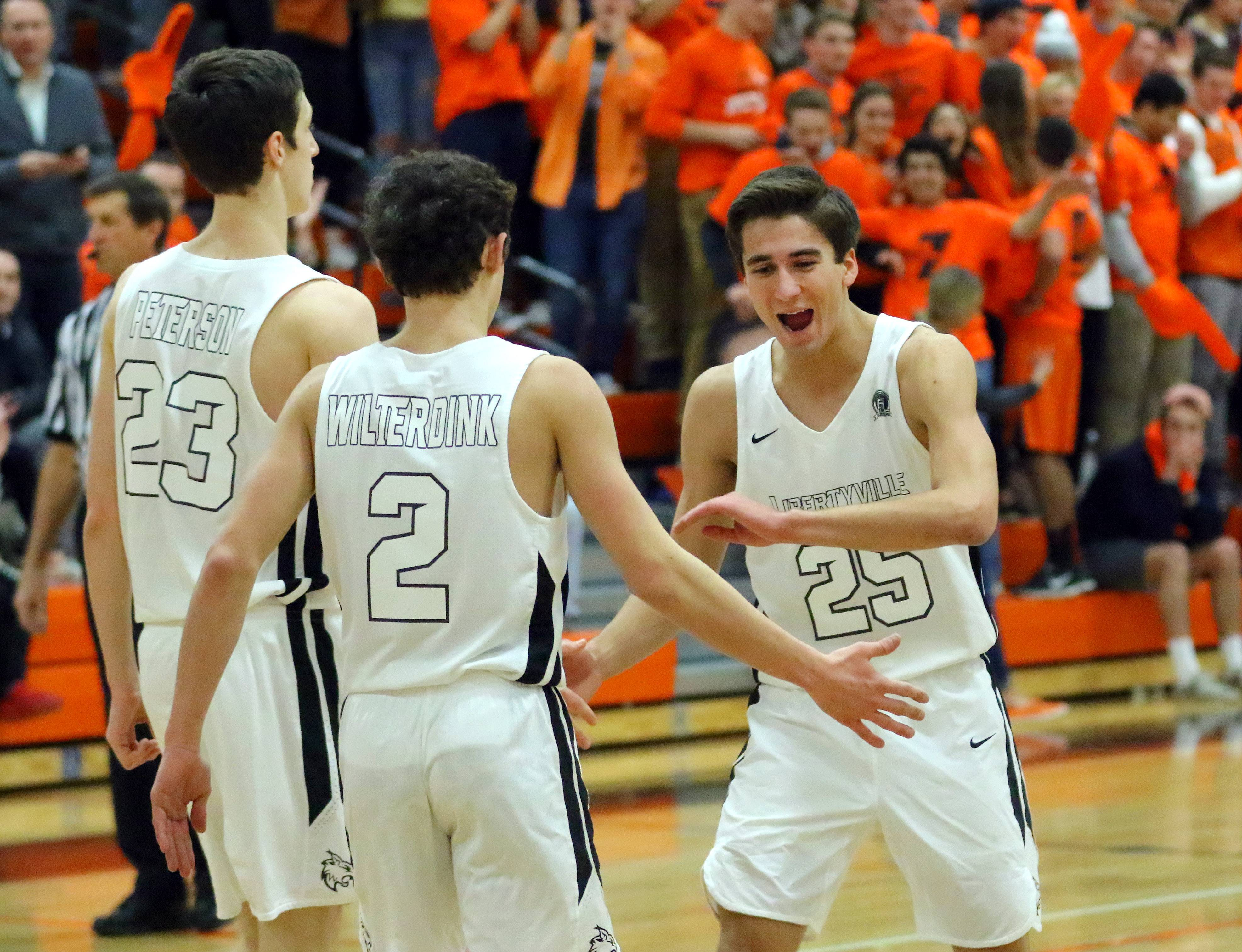 Libertyville's Chase Eyre (25) celebrates with Brian Wilterdink (2) and Drew Peterson against Waukegan on Friday night in Libertyville.