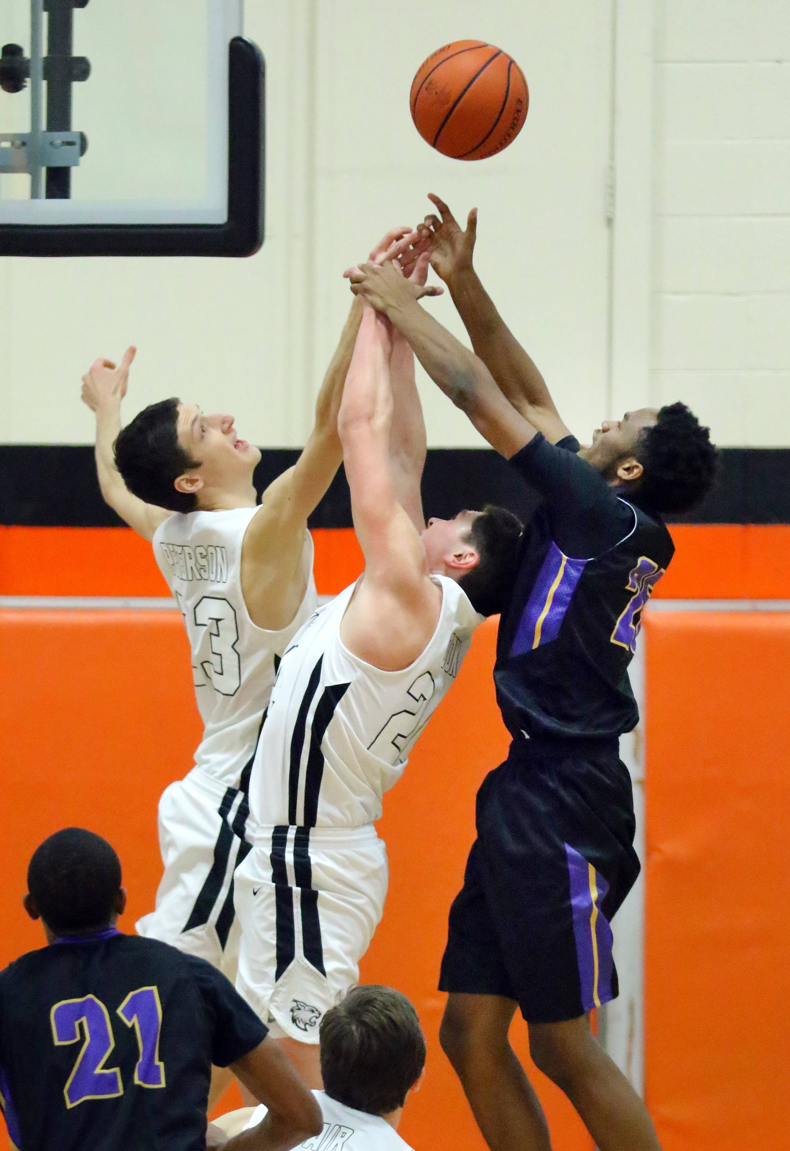 Libertyville's Drew Peterson, left, and Brendan Cook battle for a rebound with Waukegan's Bryant Brown on Friday night in Libertyville.