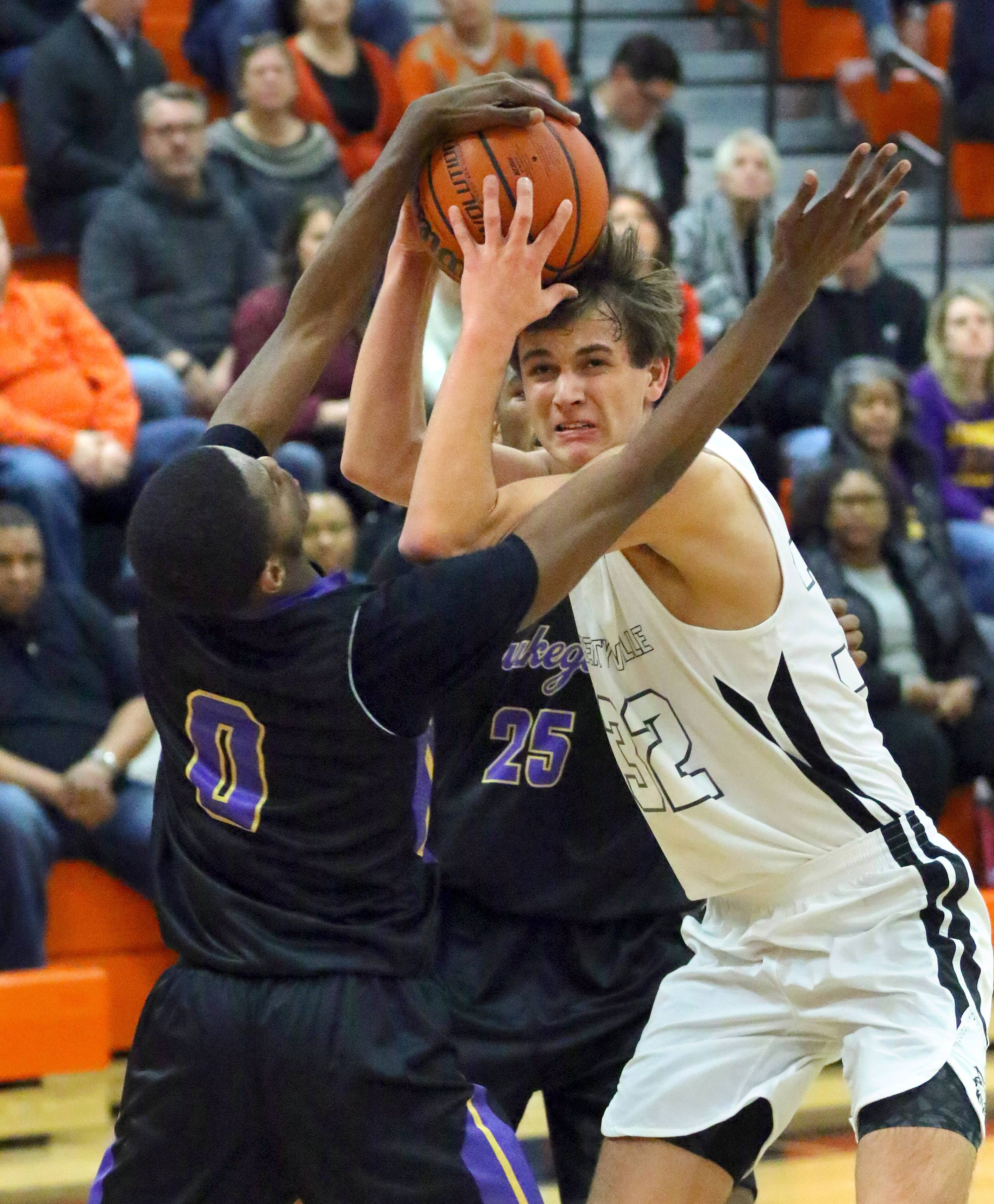Libertyville's Travis Clark, right, battles for a rebound with Waukegan's Jaylin Cunningham (0) and Bryant Brown on Friday night in Libertyville.
