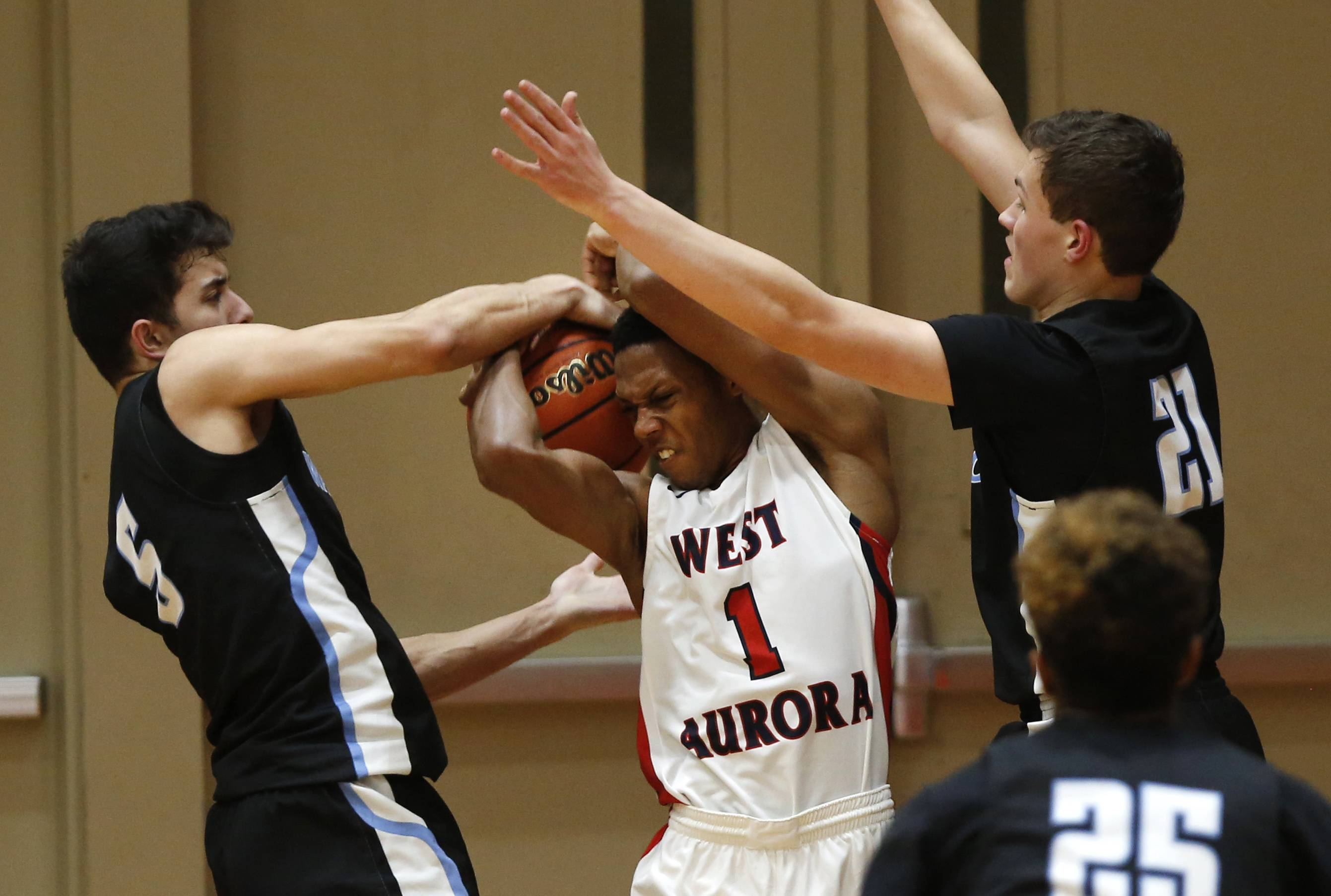 West Aurora's Traevon Brown (1) is double teamed by Willowbrook's Sikander Zafar (5) and Matas Masys (21) during the 25th annual Jim & Sylvia Roberts Night of Hoops boys basketball game at Batavia High School.
