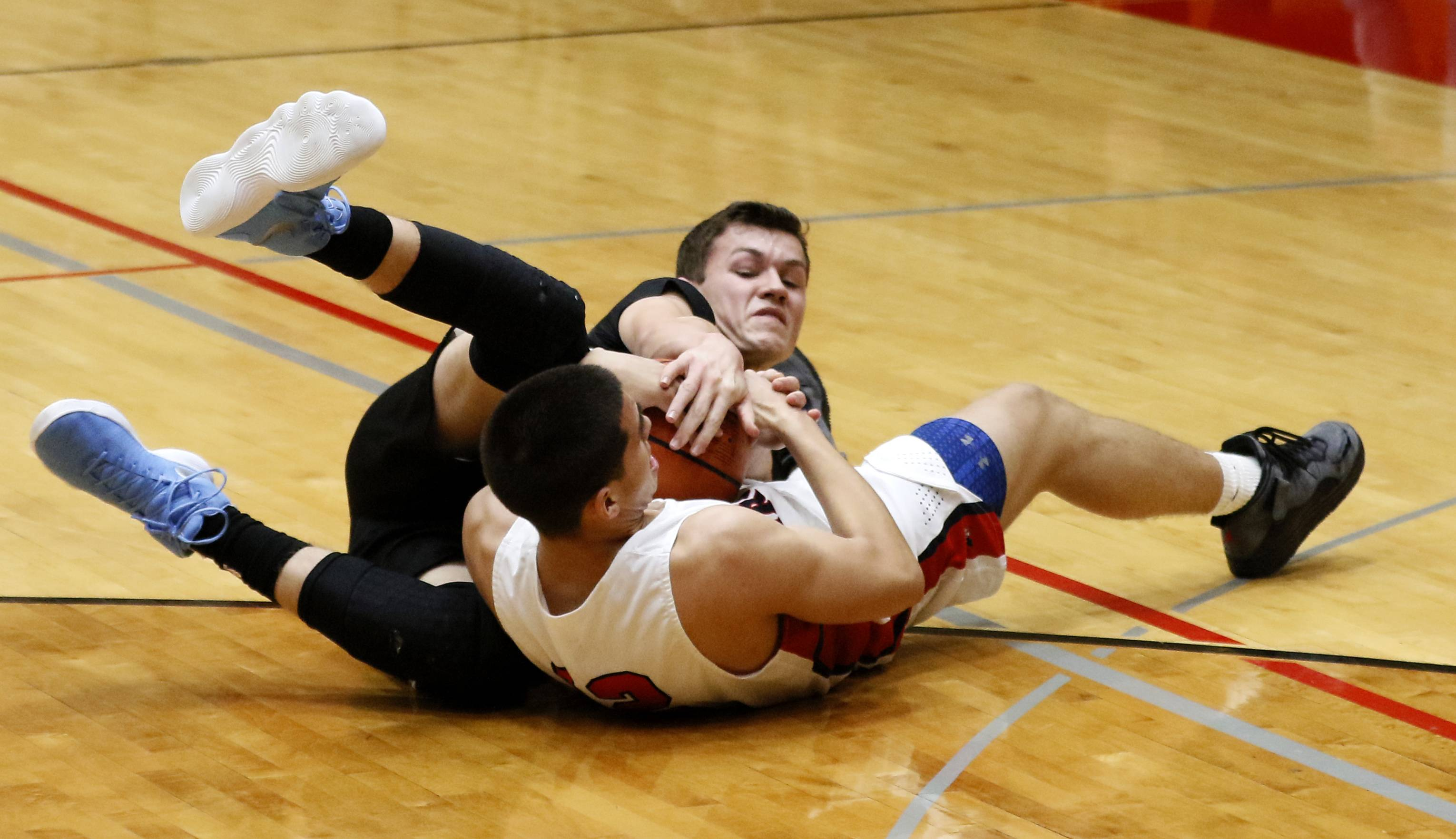 Willowbrook's Ethan Chuemer, behind, battles for a loose ball with West Aurora's Damian Virgen, right, during the 25th annual Jim & Sylvia Roberts Night of Hoops boys basketball game at Batavia High School.