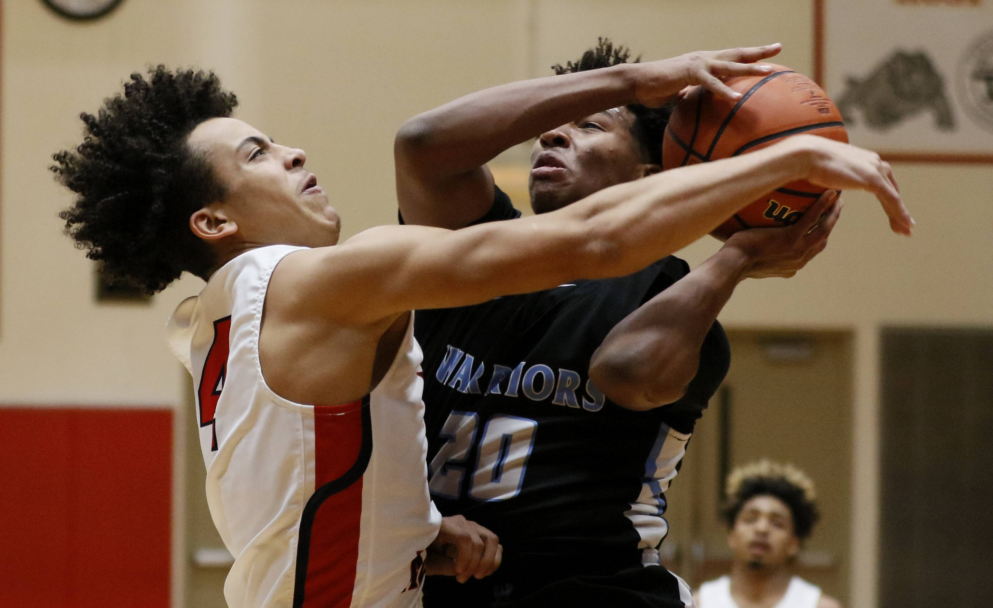 West Aurora's Moshe Rogers, left, defends the lane against Willowbrook's Matthew Myers Saturday during the 25th annual Jim & Sylvia Roberts Night of Hoops boys basketball game at Batavia High School.