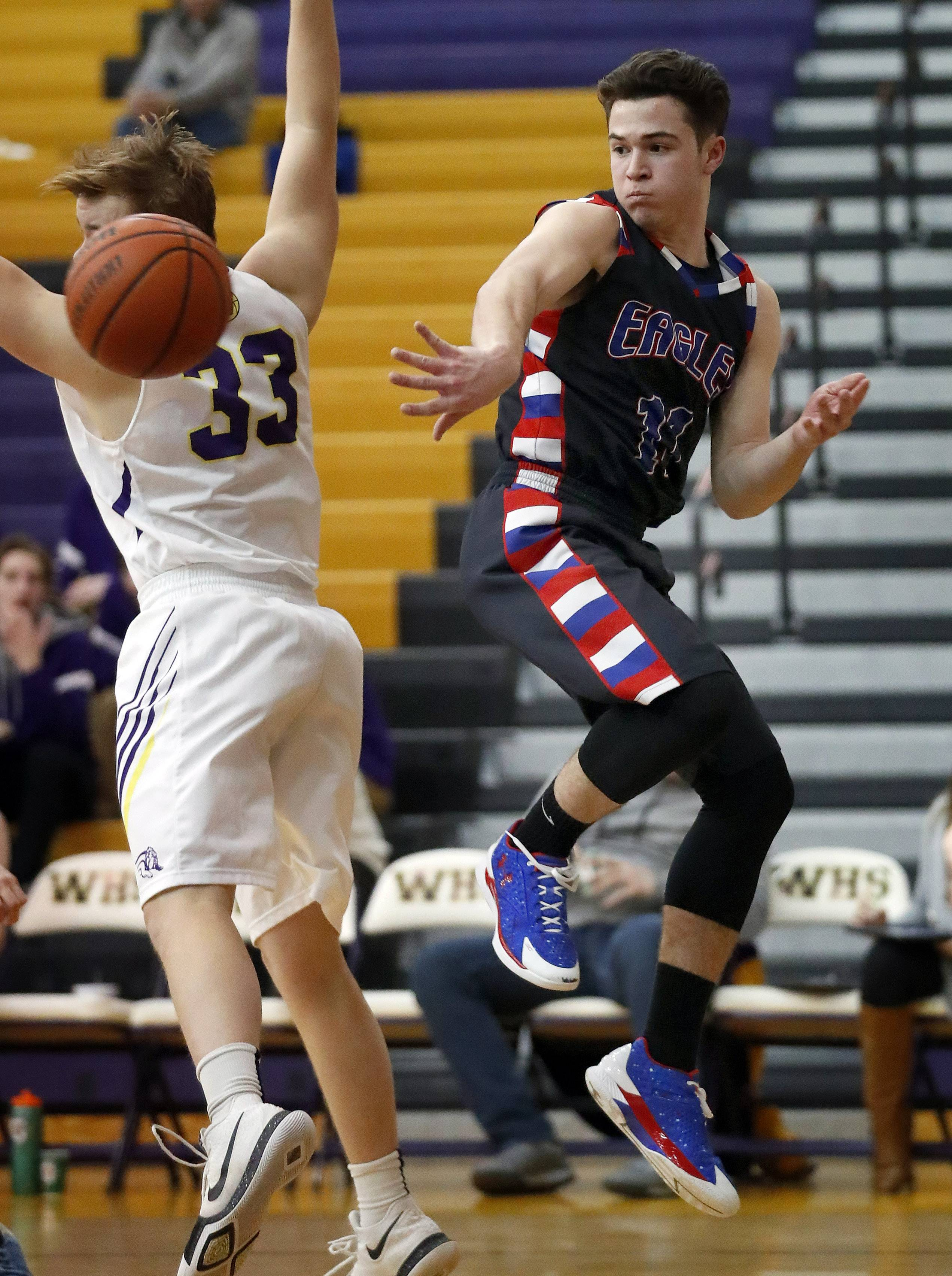 Lakes' Michael Behrendt, right, dishes the ball off around Wauconda's Andrew Nolan on Tuesday night in Wauconda.