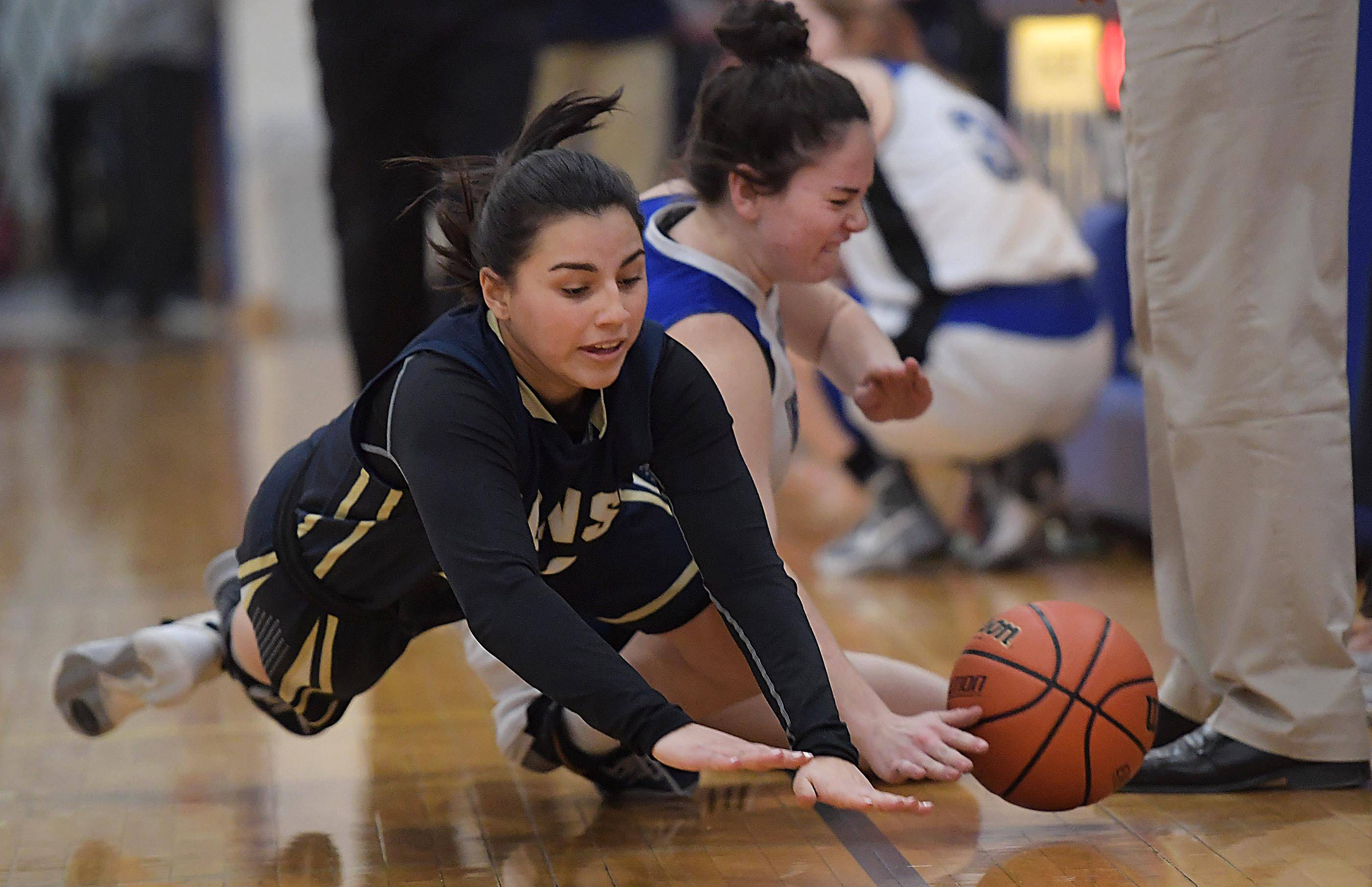 Harvest Christian's Isamar Garcia and Rosary's Maura Vanbogaert tumble out-of-bounds in a girls basketball game in Aurora Tuesday.