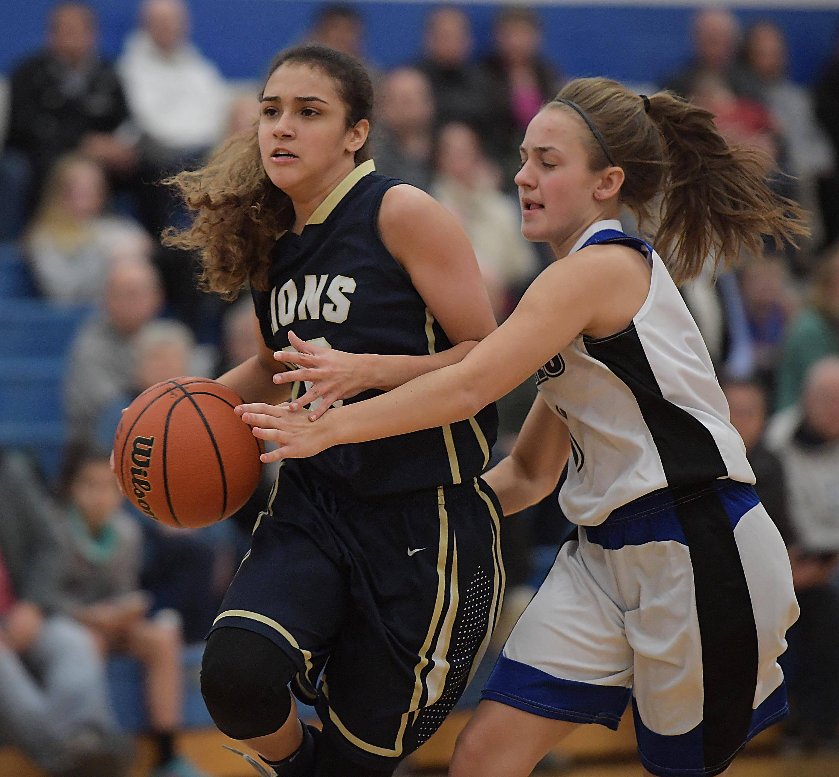 Rosary's Kristin Timko gets her hand on the ball as Harvest Christian's Alyssa Iverson runs past in a girls basketball game in Aurora Tuesday.