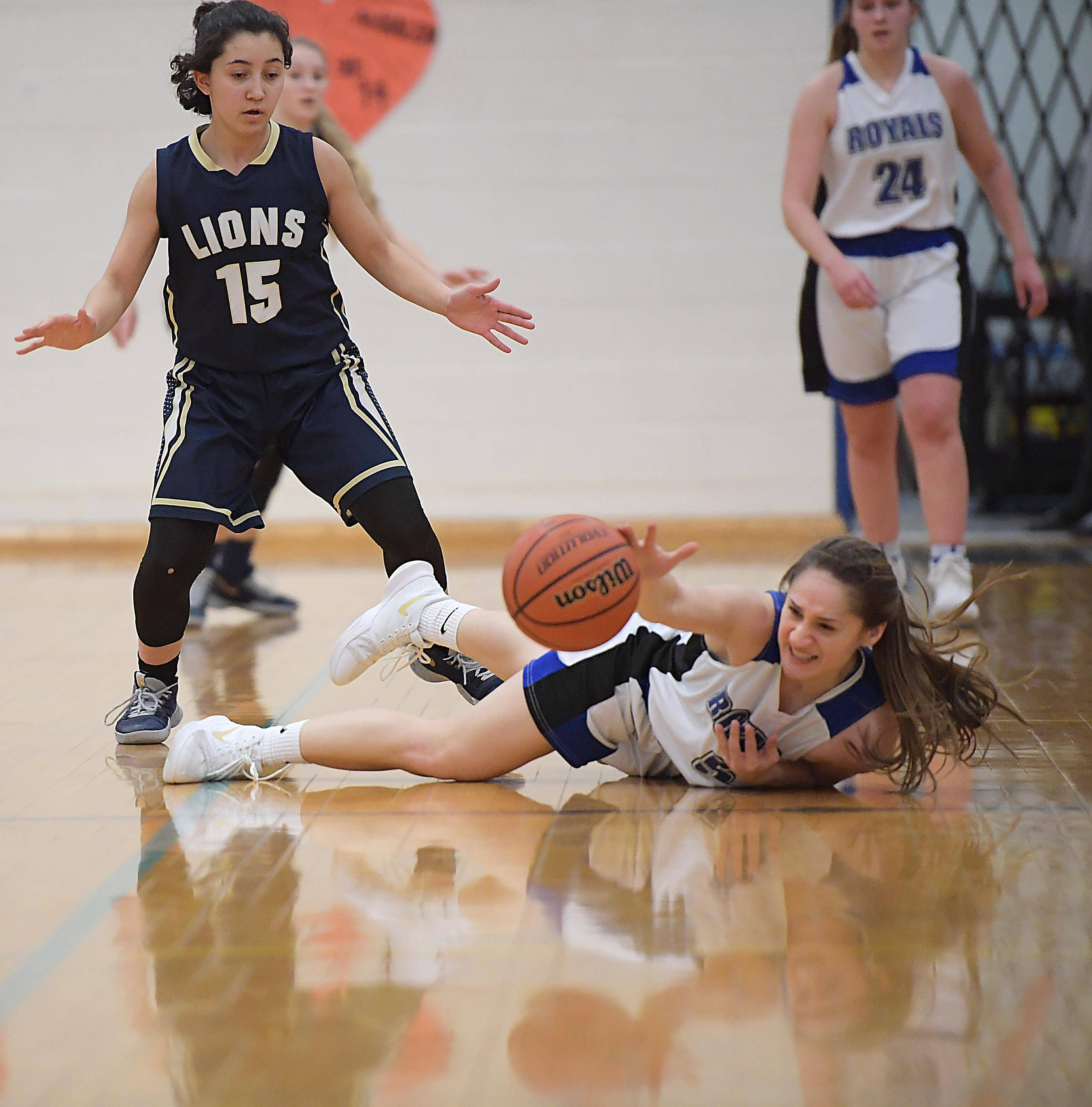 Rosary's Jenna Hernandez loses the ball out of bounds as Harvest Christian's Elena Porrata watches in a girls basketball game in Aurora Tuesday.