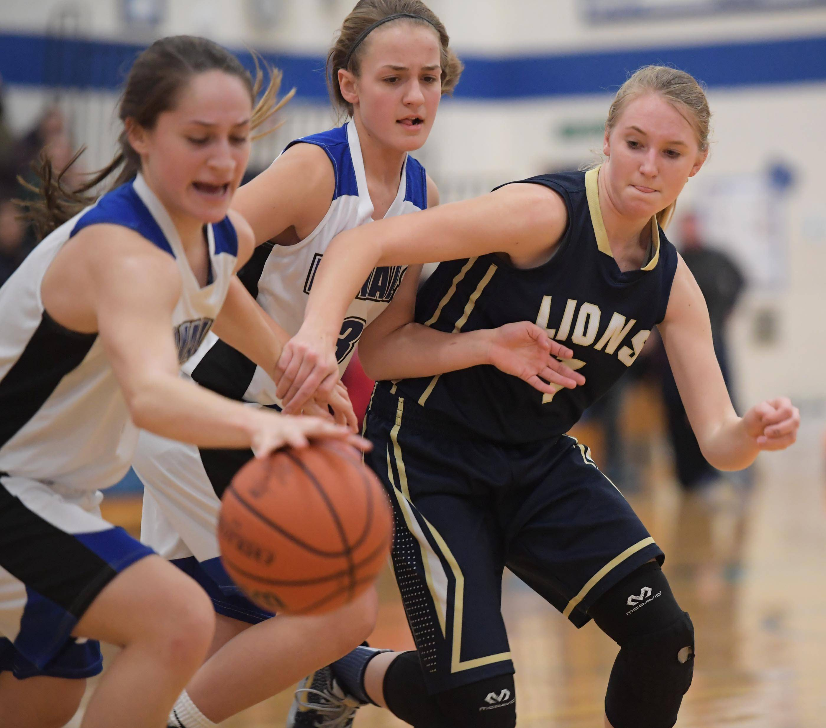 Rosary's Jenna Hernandez recovers a loose ball as teammate Kristin Timko holds back Harvest Christian's Maddy Martin in a girls basketball game in Aurora Tuesday.