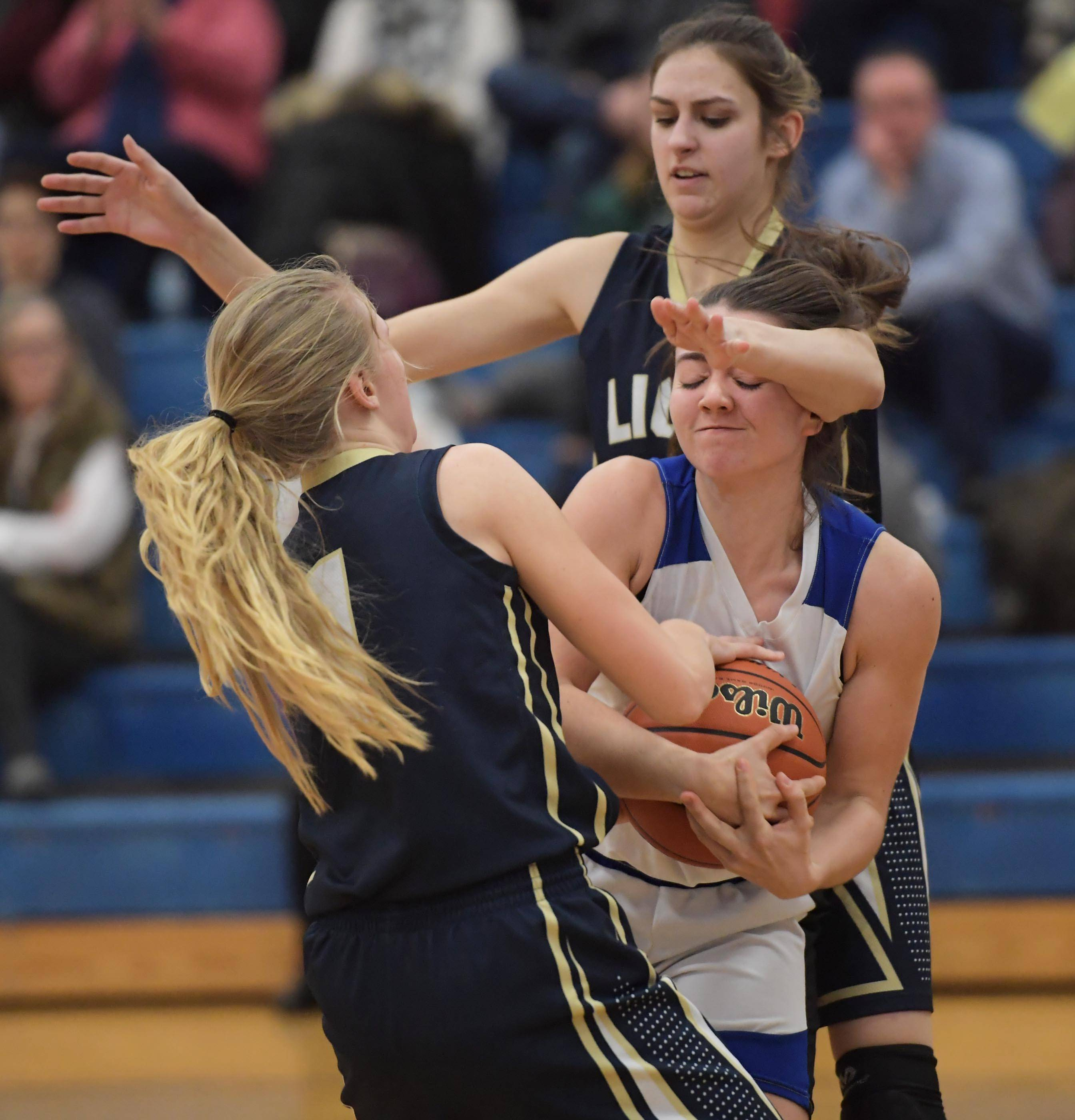 Rosary's Riley McCue struggles against Harvest Christian's Maddy Martin and Grace Ringel in a girls basketball game in Aurora Tuesday.