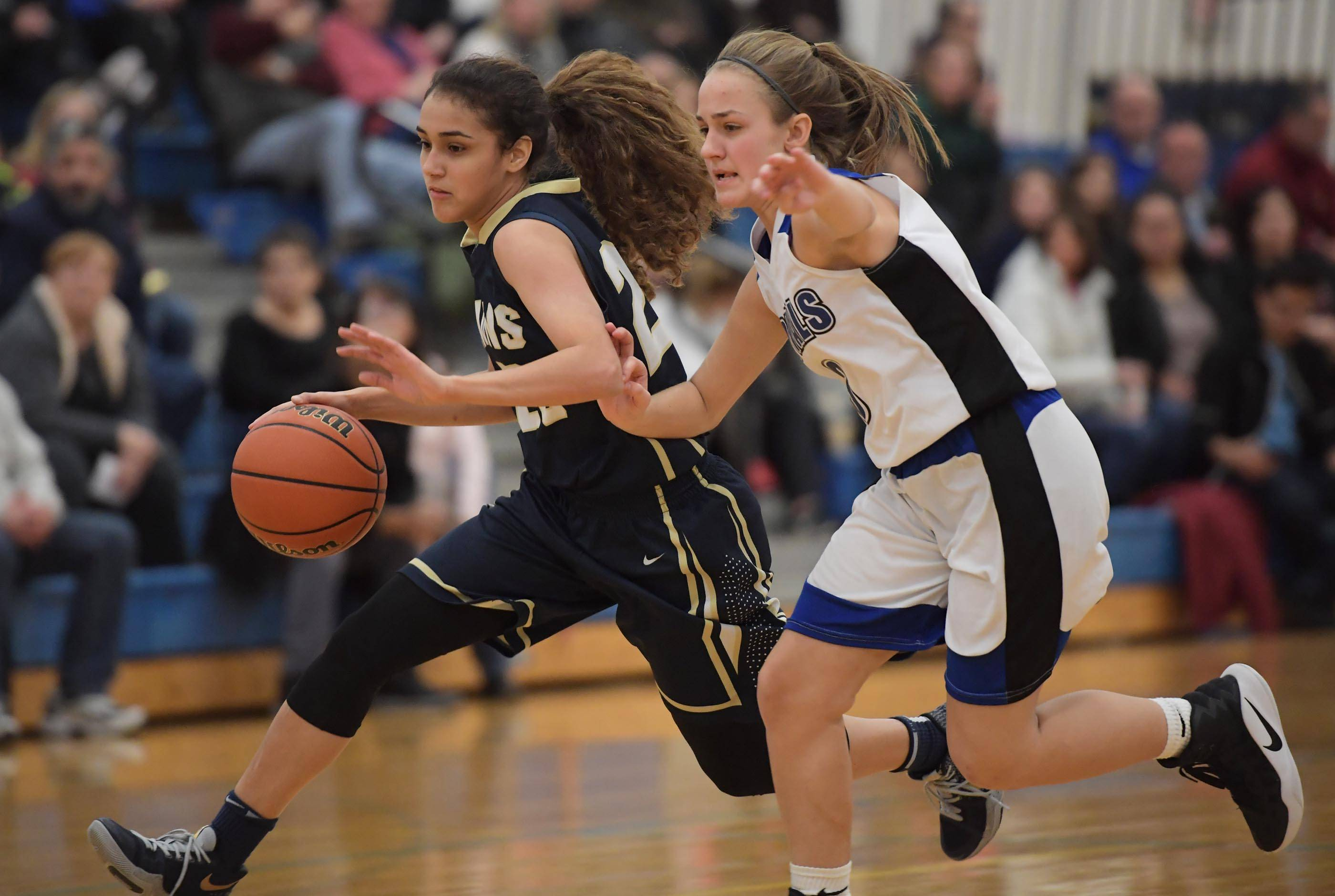 Harvest Christian's Alyssa Iverson runs past Rosary's Kristin Timko in a girls basketball game in Aurora Tuesday.