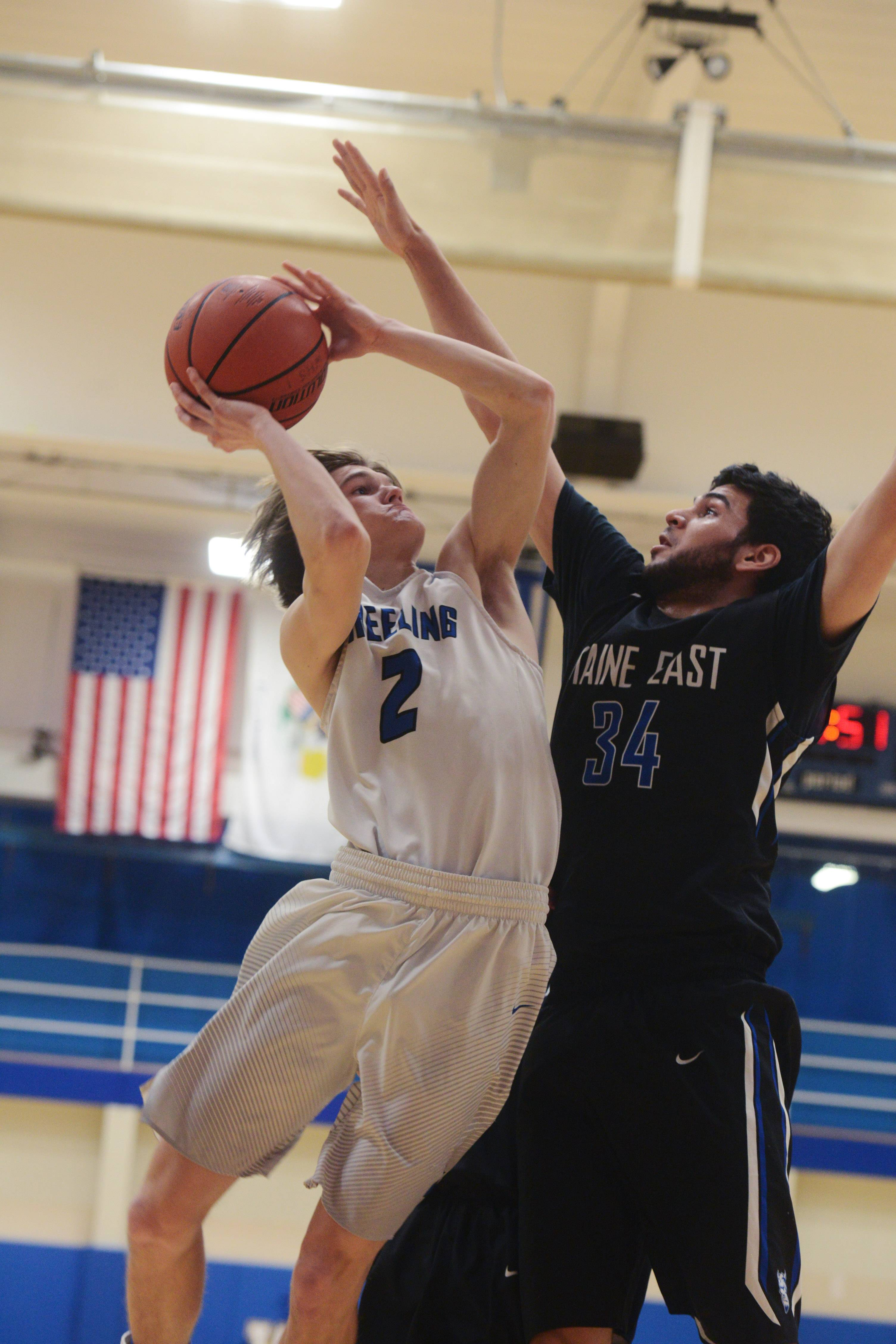 Wheeling's DJ Godlewski, left, drives to the basket against Maine East's Kyle Gilani during Tuesday's game at Wheeling.