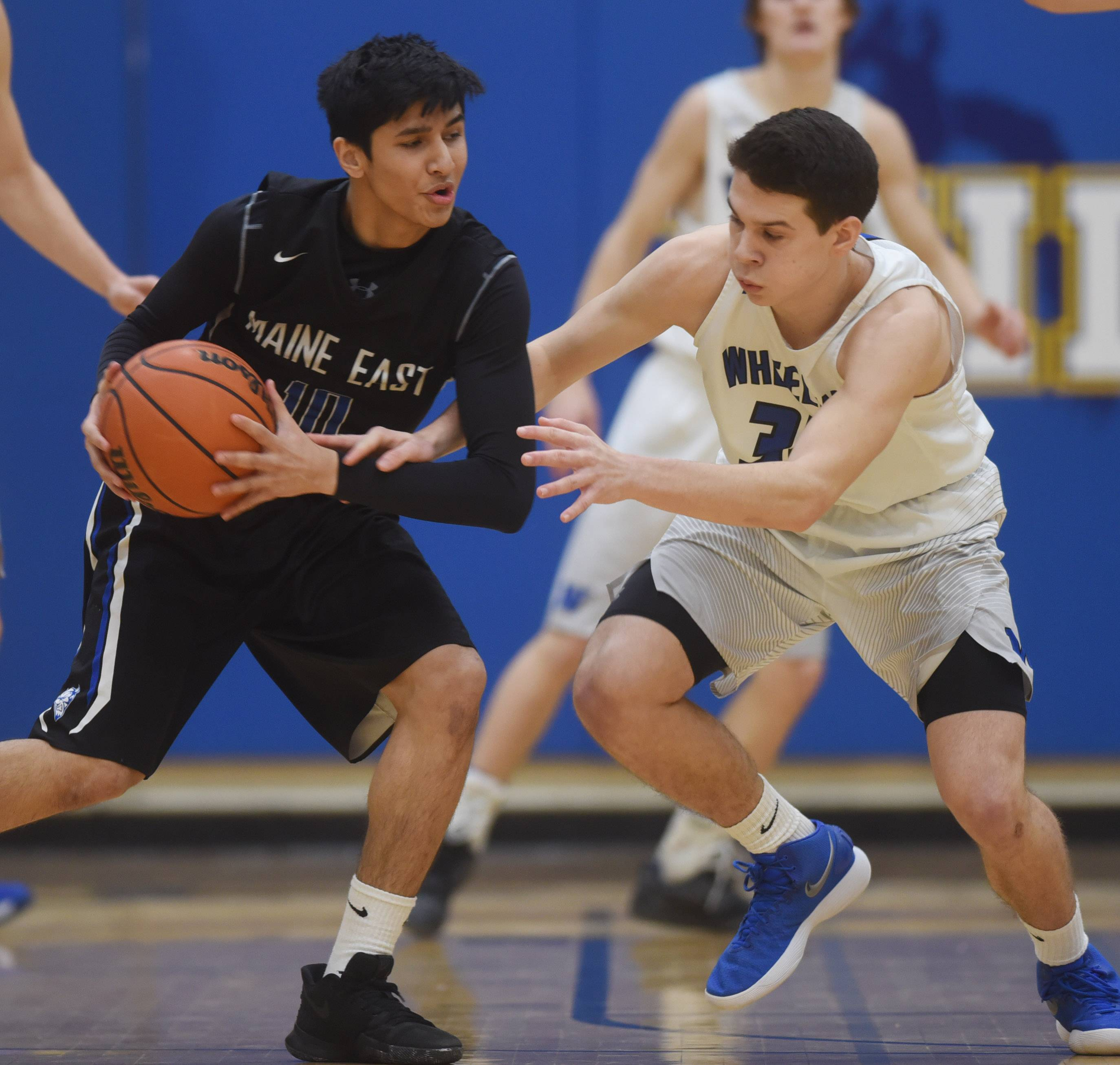 Wheeling's Brandon Zettek, right, closely guards Maine East's Justice Shaw during Tuesday's game at Wheeling.