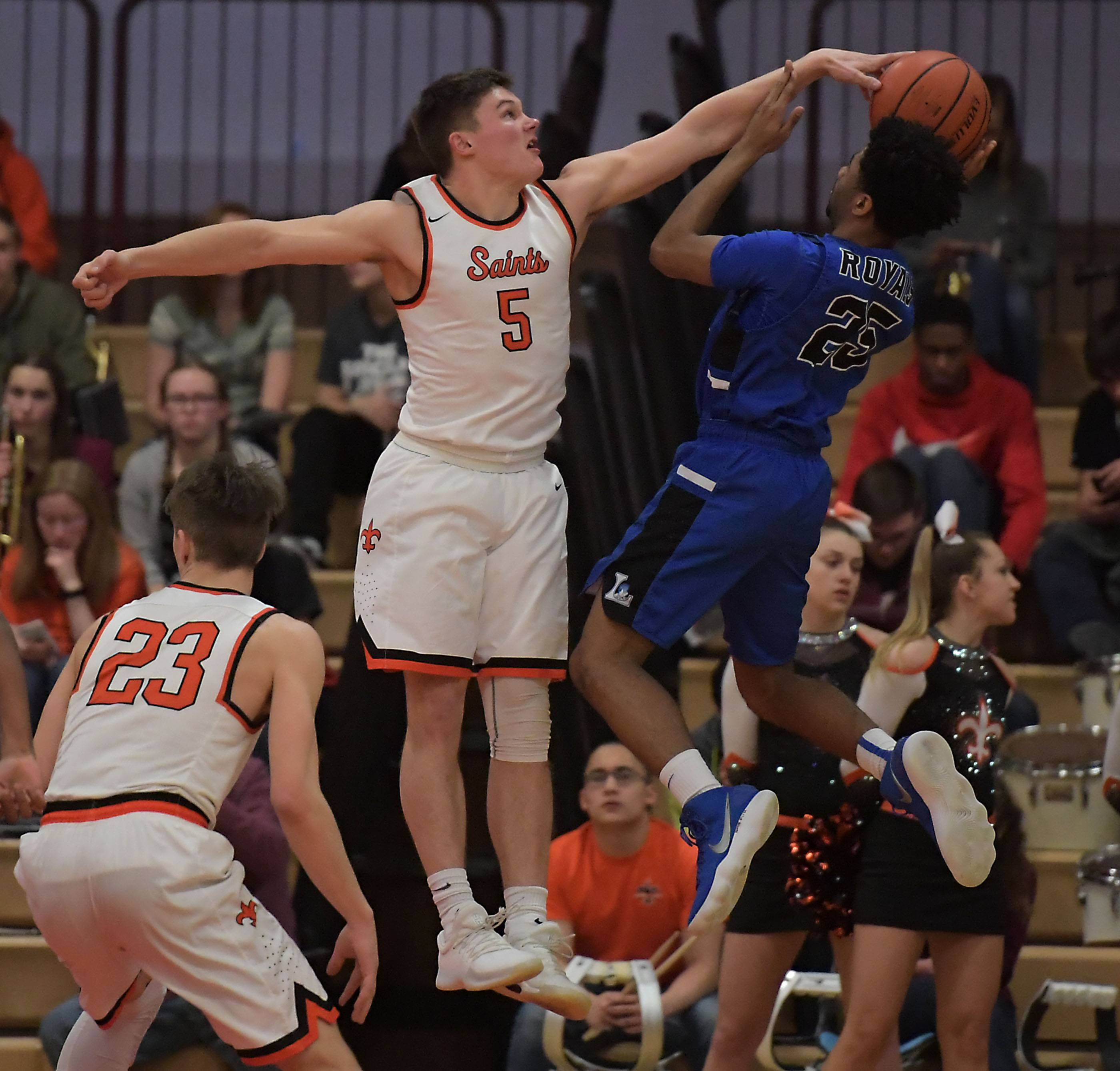 St. Charles East's Zachary Robinson blocks the shot of Larkin's Christopher Rose Thursday in a boys basketball game in St. Charles.