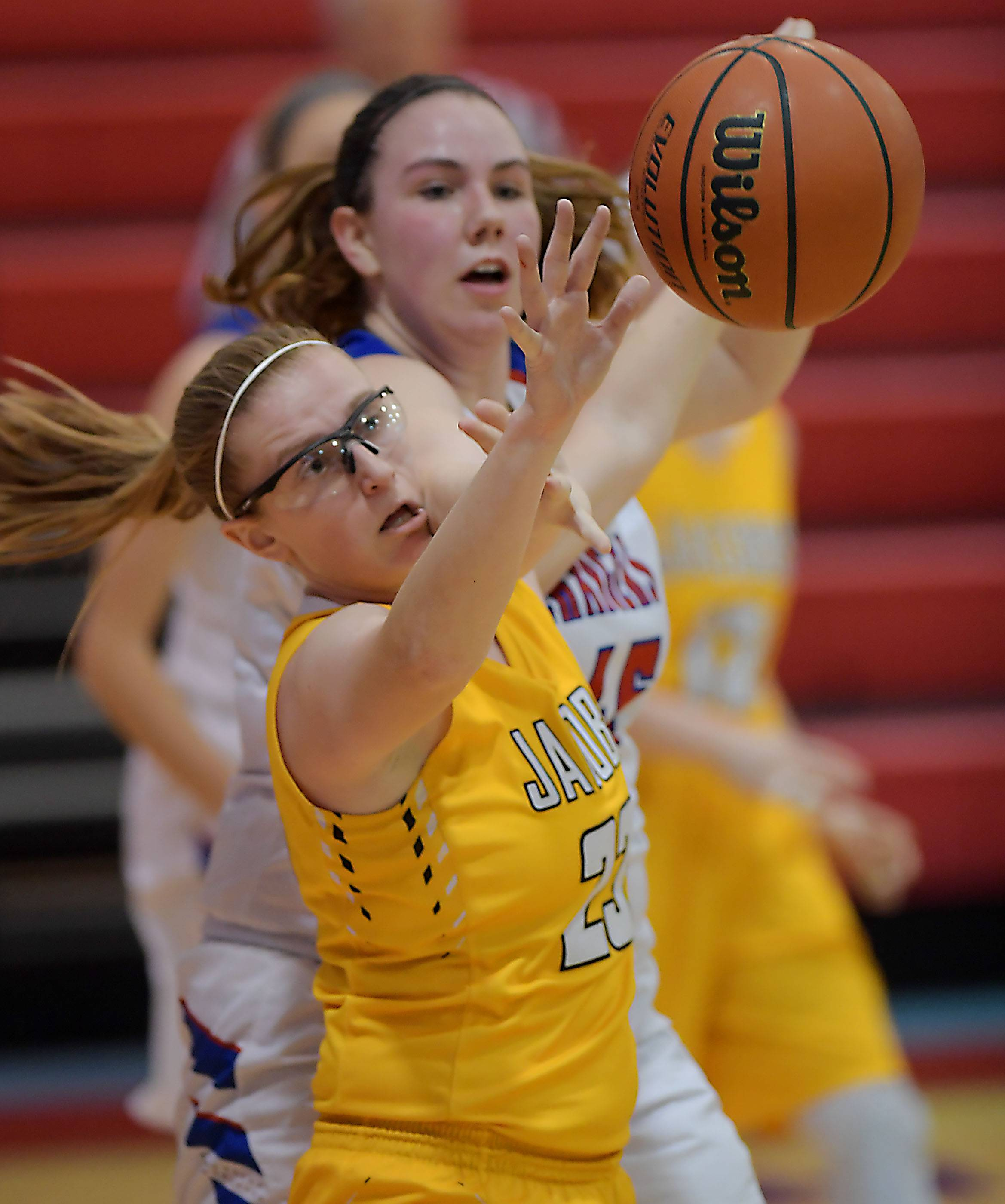 Jacobs' Kerri Healy reaches a rebound in front of Dundee-Crown's Madilyn Tripp Saturday in a girls basketball game in Carpentersville.