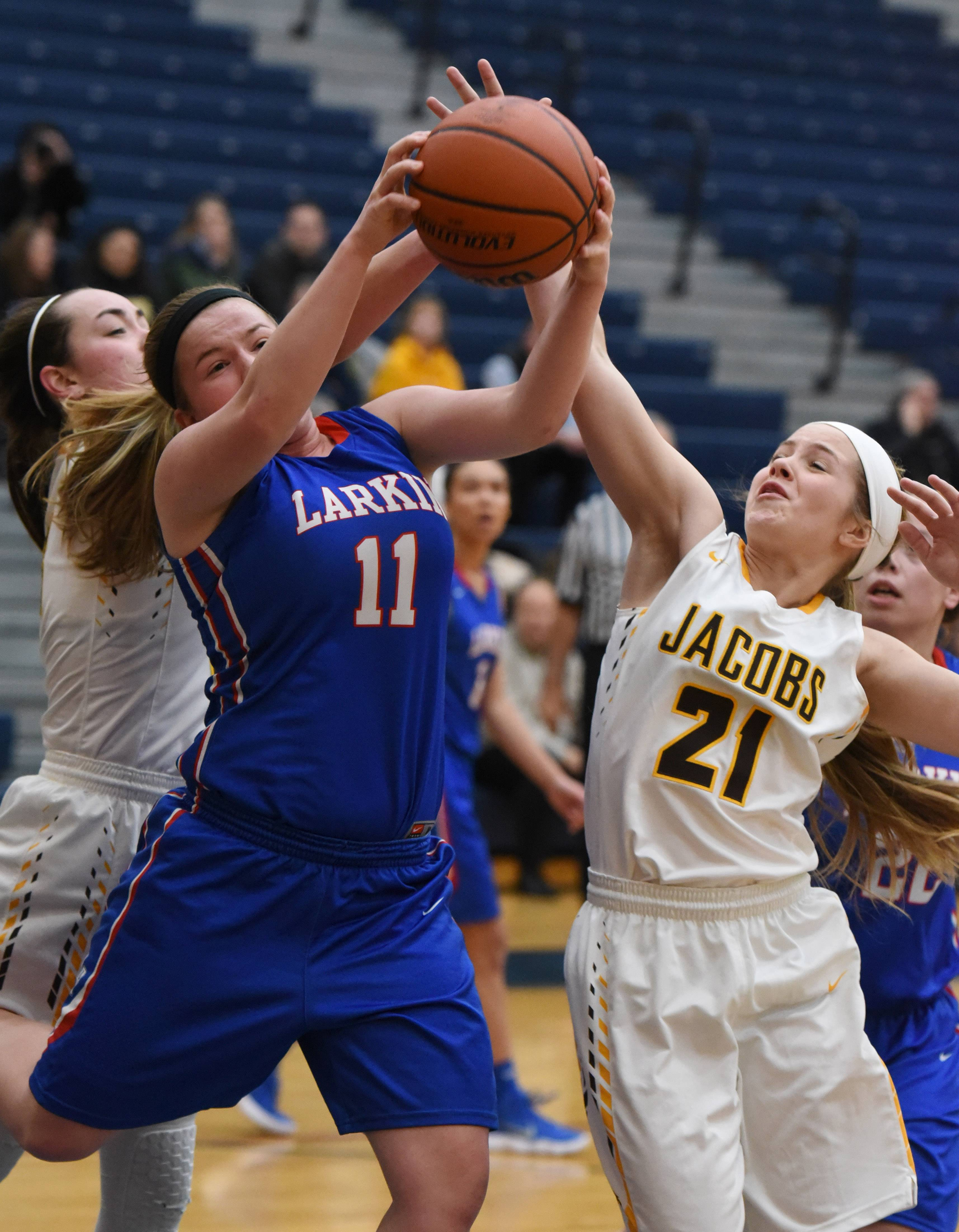 Larkin's Haley Bohne (11) and Jacobs' Delaney Garden fight for a rebound during Monday's Class 4A South Elgin regional girls basketball game.