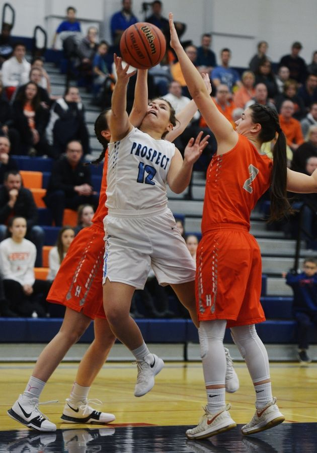 Prospect's Margherite Pettenuzzo draws contact as she tries to make a move to the basket between Hersey's Mary Kate Fahey, left, and Maesyn Benjamin during the Class 4A girls basketball regional semifinal at Buffalo Grove on Tuesday.