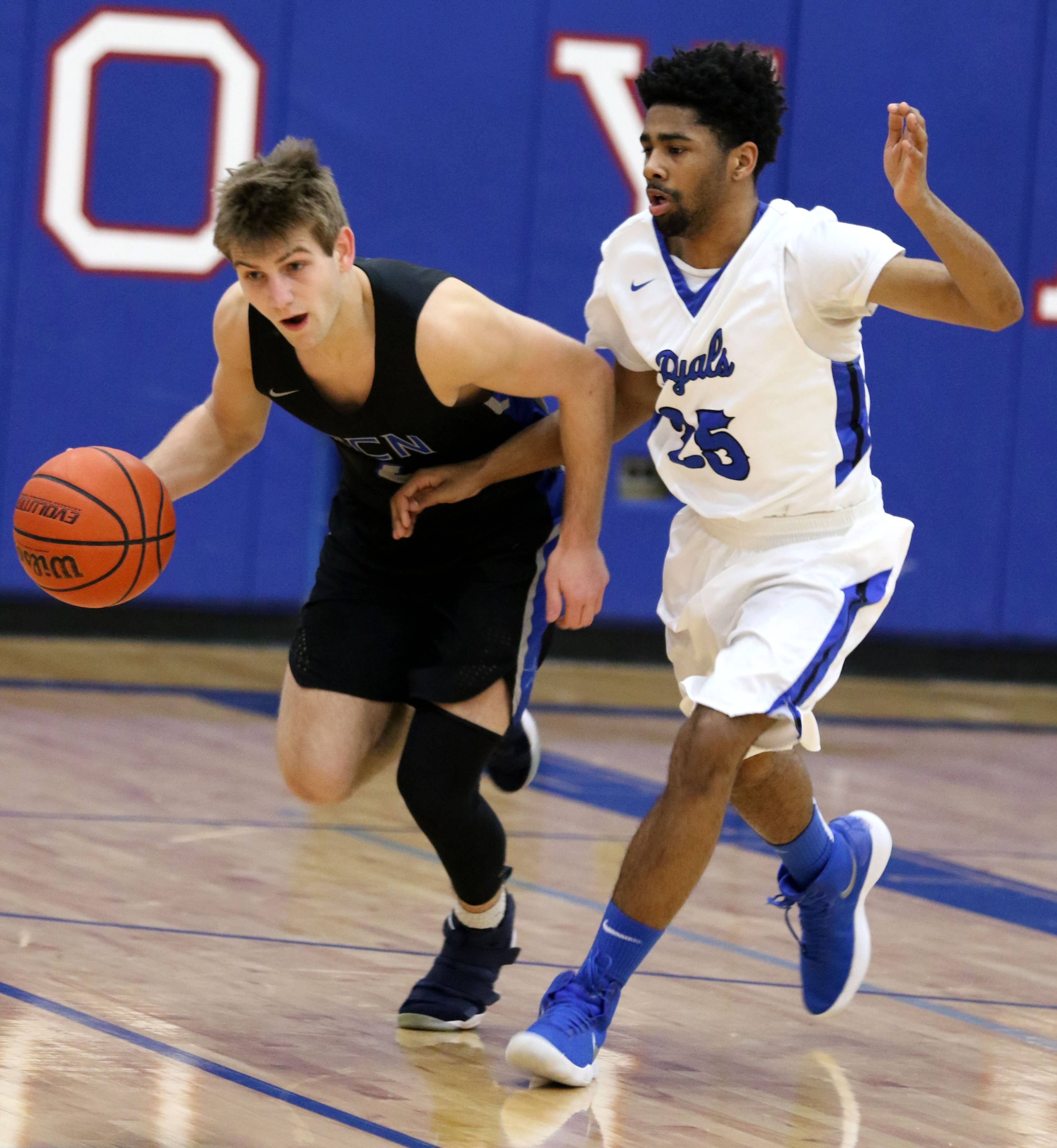 St. Charles North's Zachary Ludwig, left, works the ball past Larkin's Christopher Rose during a varsity boys basketball game at Larkin High School in Elgin Friday night.