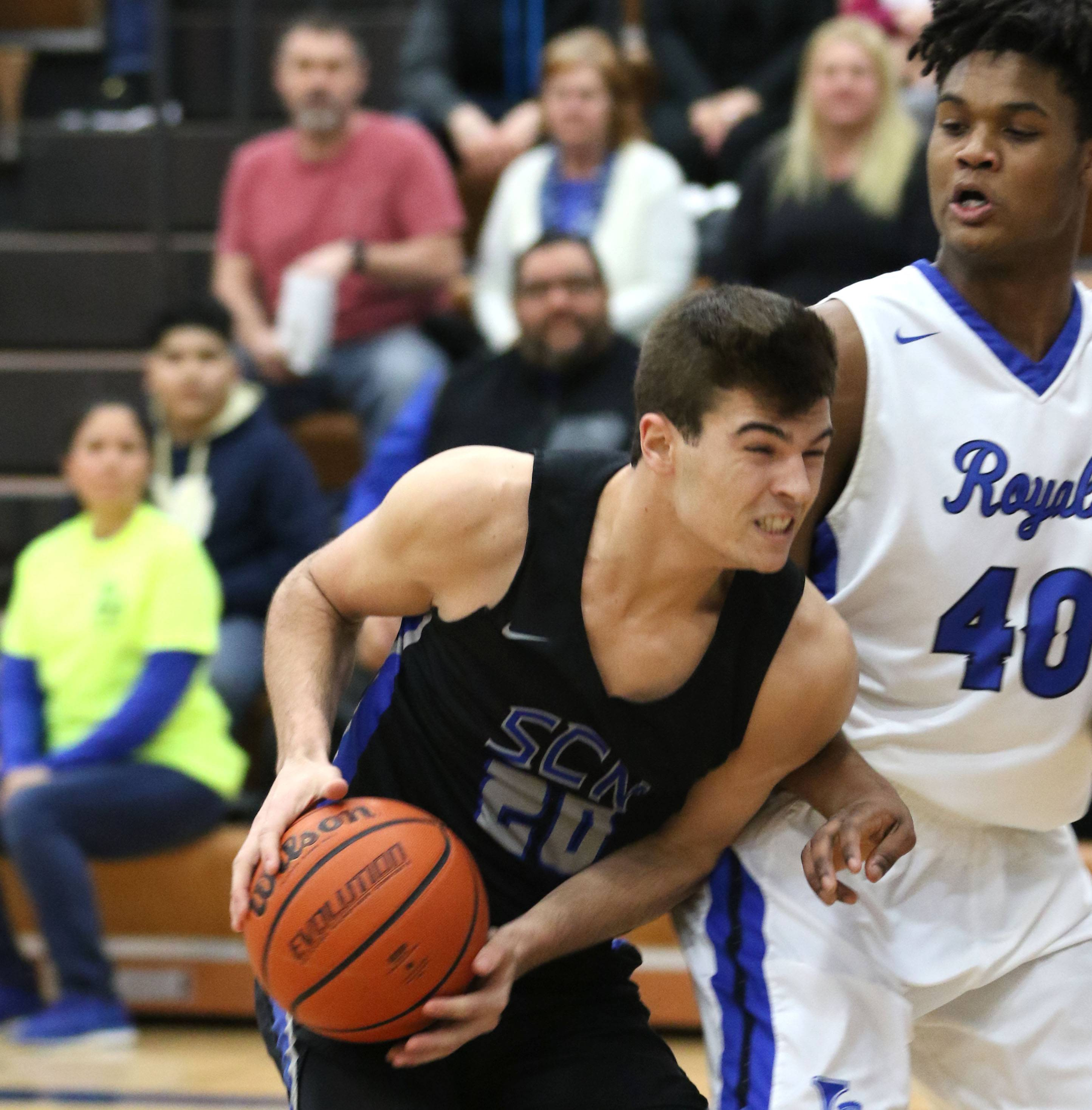 St. Charles North's Kyle King battles to the hoop against Larkin's Jalen Shaw during a varsity boys basketball game at Larkin High School in Elgin Friday night.