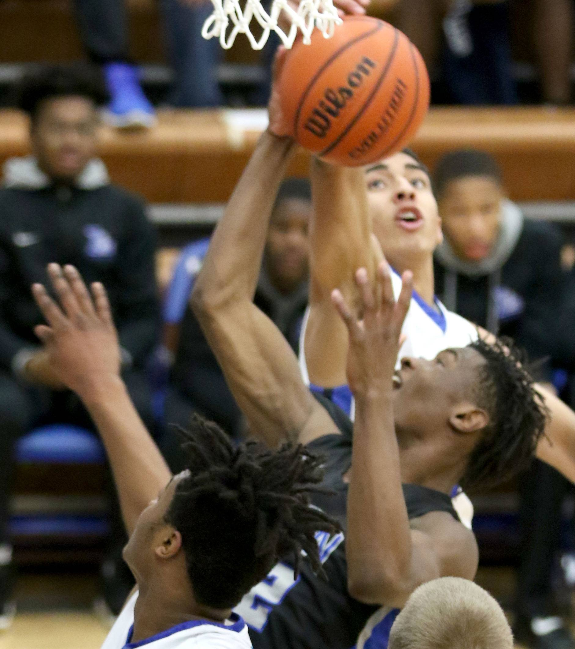 St. Charles North's Tyler Nubin, center, battles for a rebound with Larkin's Jalen Shaw, front, and Victor Perez, back, during a varsity boys basketball game at Larkin High School in Elgin Friday night.