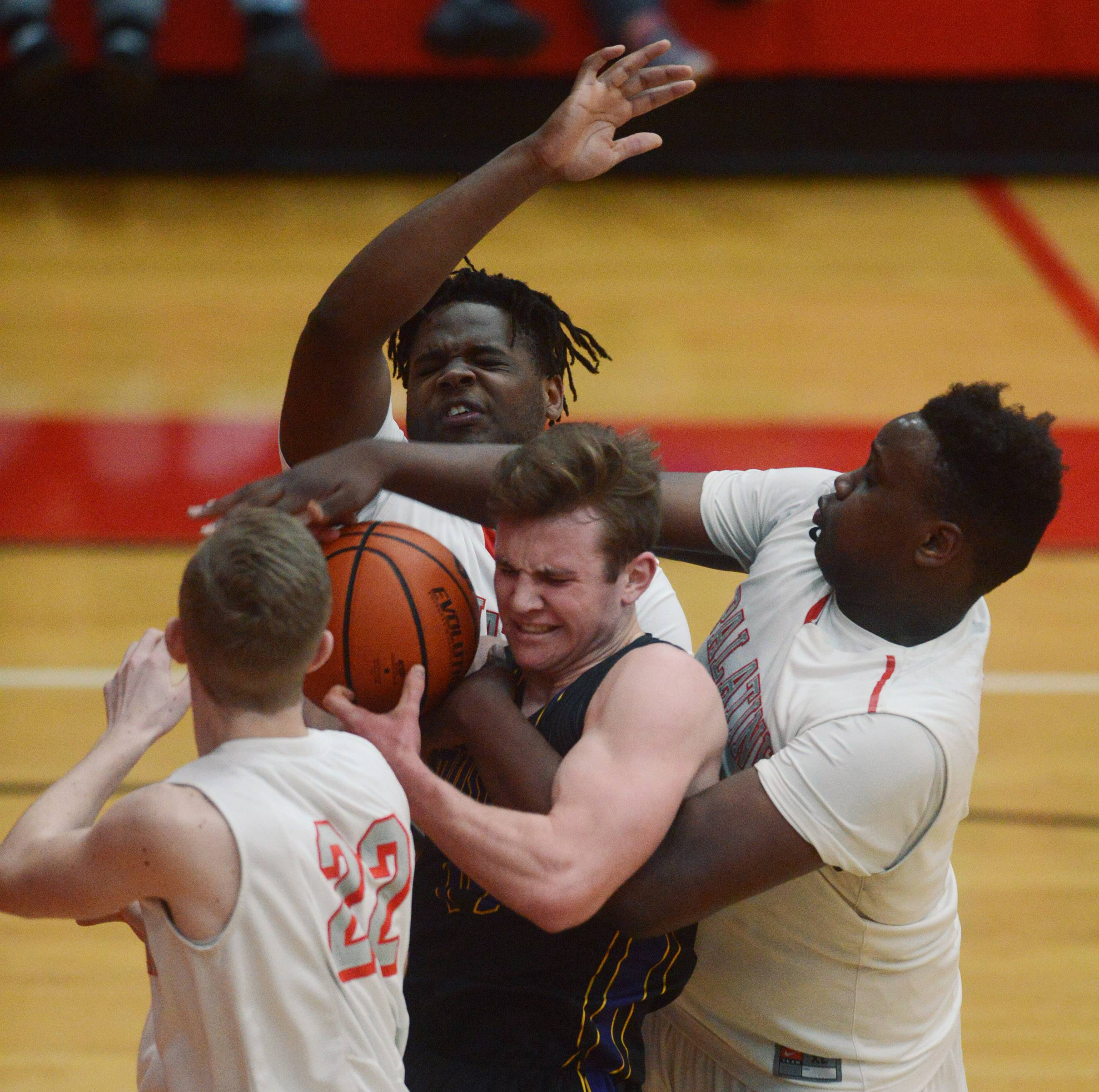 Left to right, Palatine's Ben Storm, David Balanganayi and Julian Campbell surround Rolling Meadows' Sean Nolan under the Mustangs' basket during Tuesday's game at Palatine.