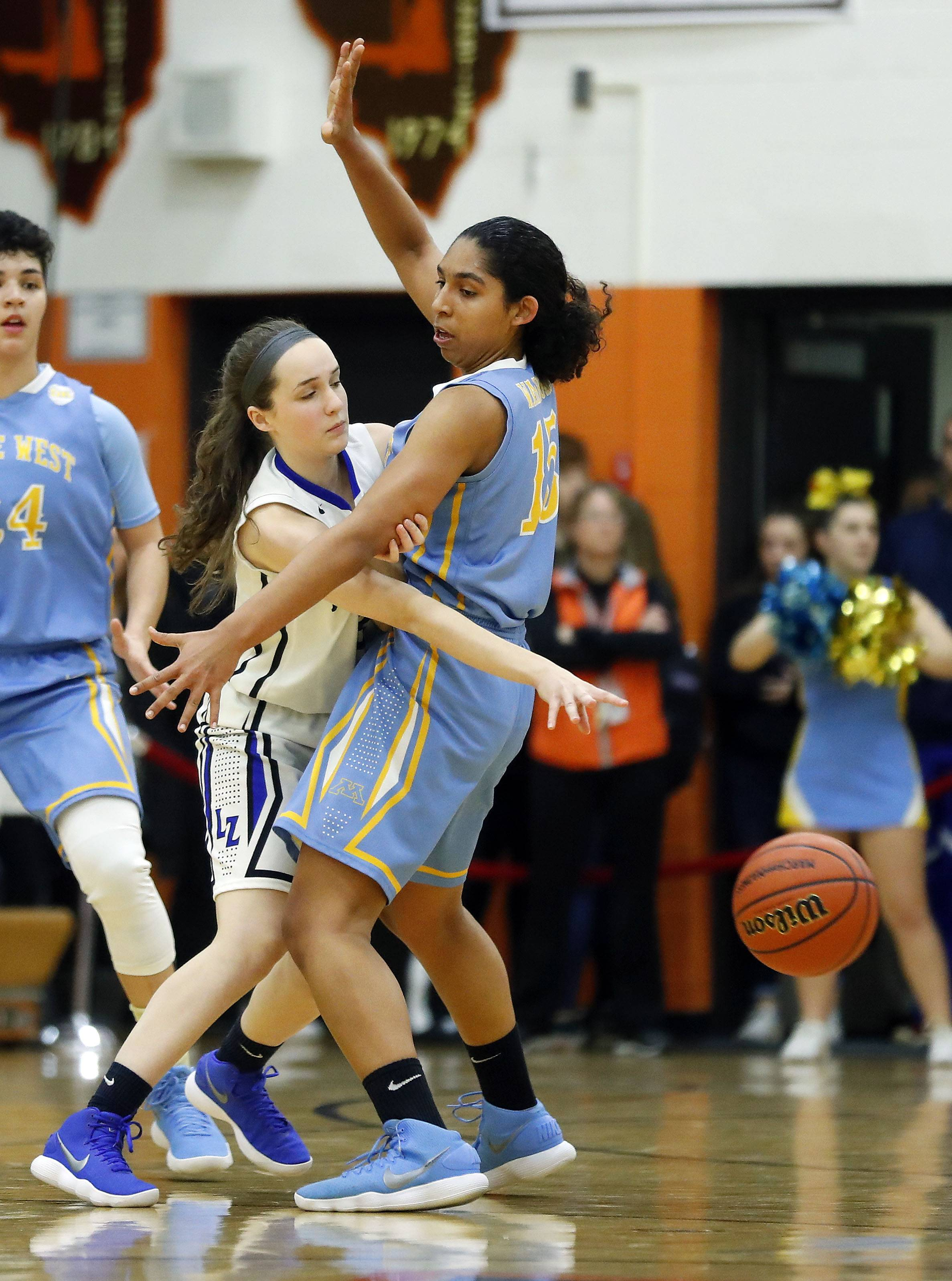 Lake Zurich's Margueret Spear, left, passes arounds Maine West's Rachel Kent during the Class 4A Hersey supersectional in Arlington Heights on Monday.