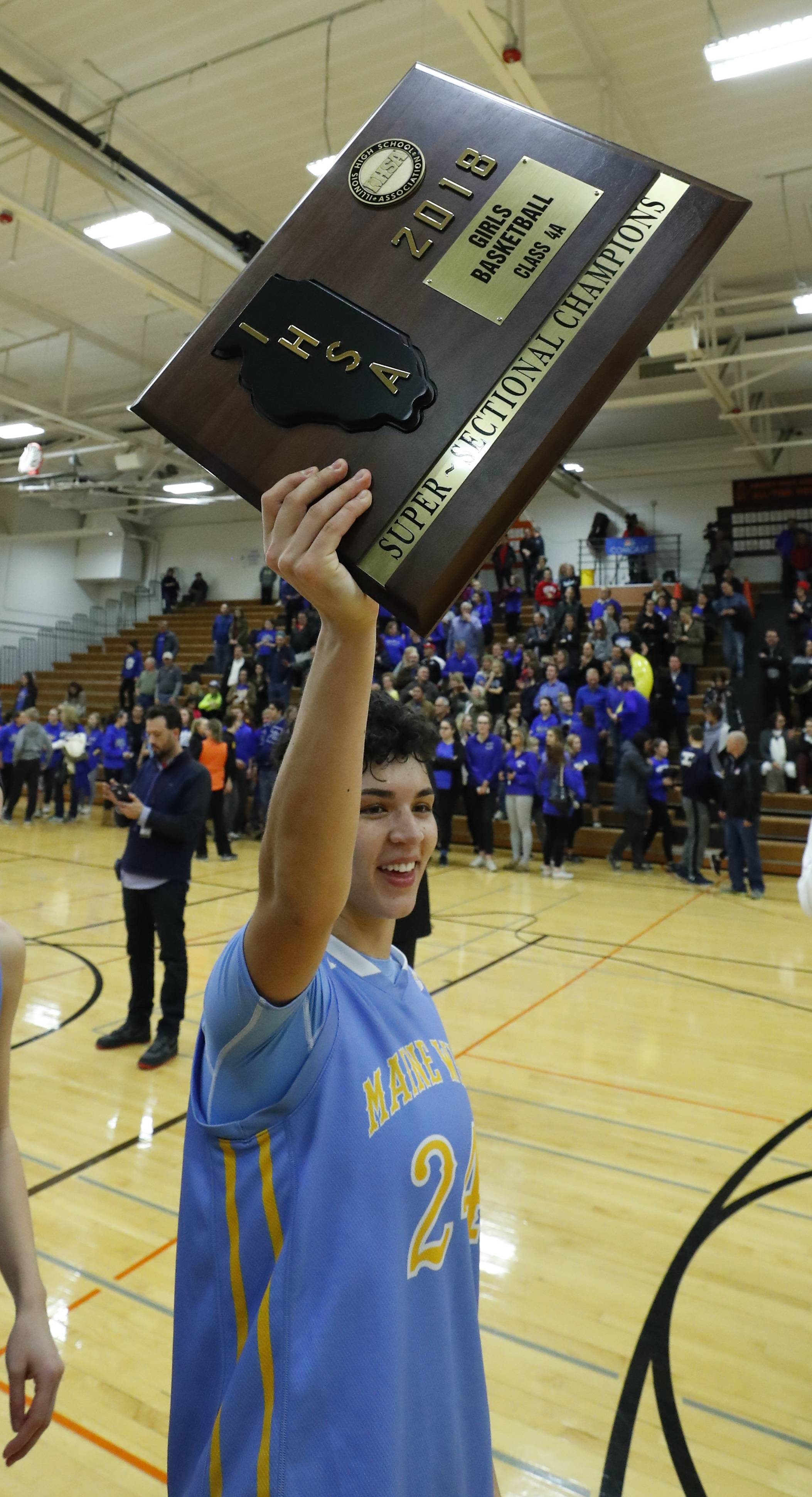 Maine West's Alisa Fallon holds the trophy after the Warriors' 52-42 win over Lake Zurich in the Class 4A Hersey supersectional in Arlington Heights on Monday.