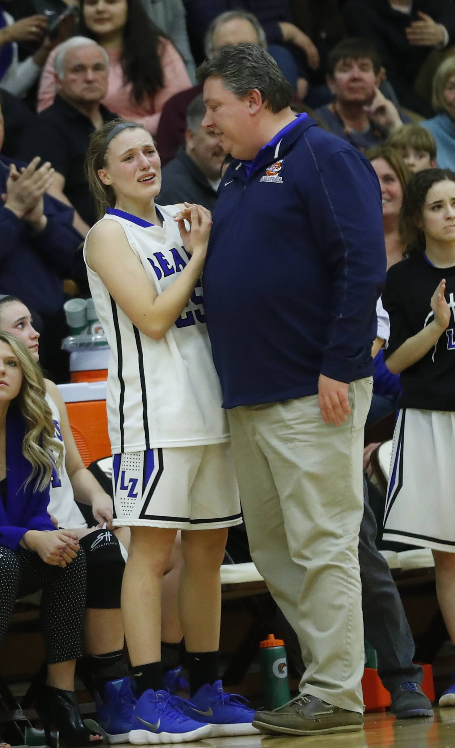 Lake Zurich's Maddy Piggott is consoled by coach Chris Bennett after fouling out of the Class 4A supersectional at Hersey High School in Arlington Heights on Monday.